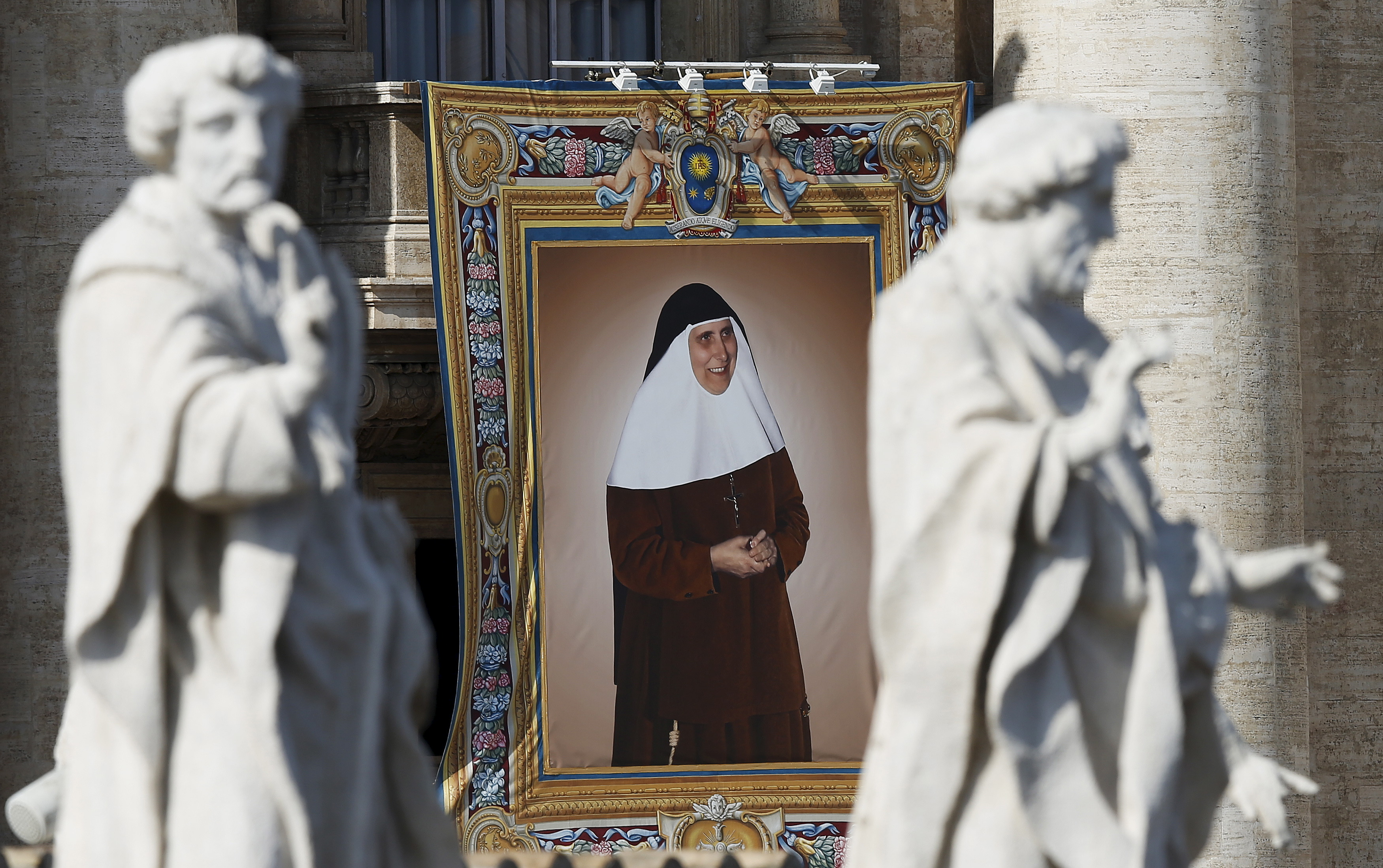 A tapestry showing Saint Mary of the Immaculate Conception hangs from a balcony as Pope Francis leads the mass for a canonization in Saint Peter's Square at the Vatican, Oct. 18, 2015.