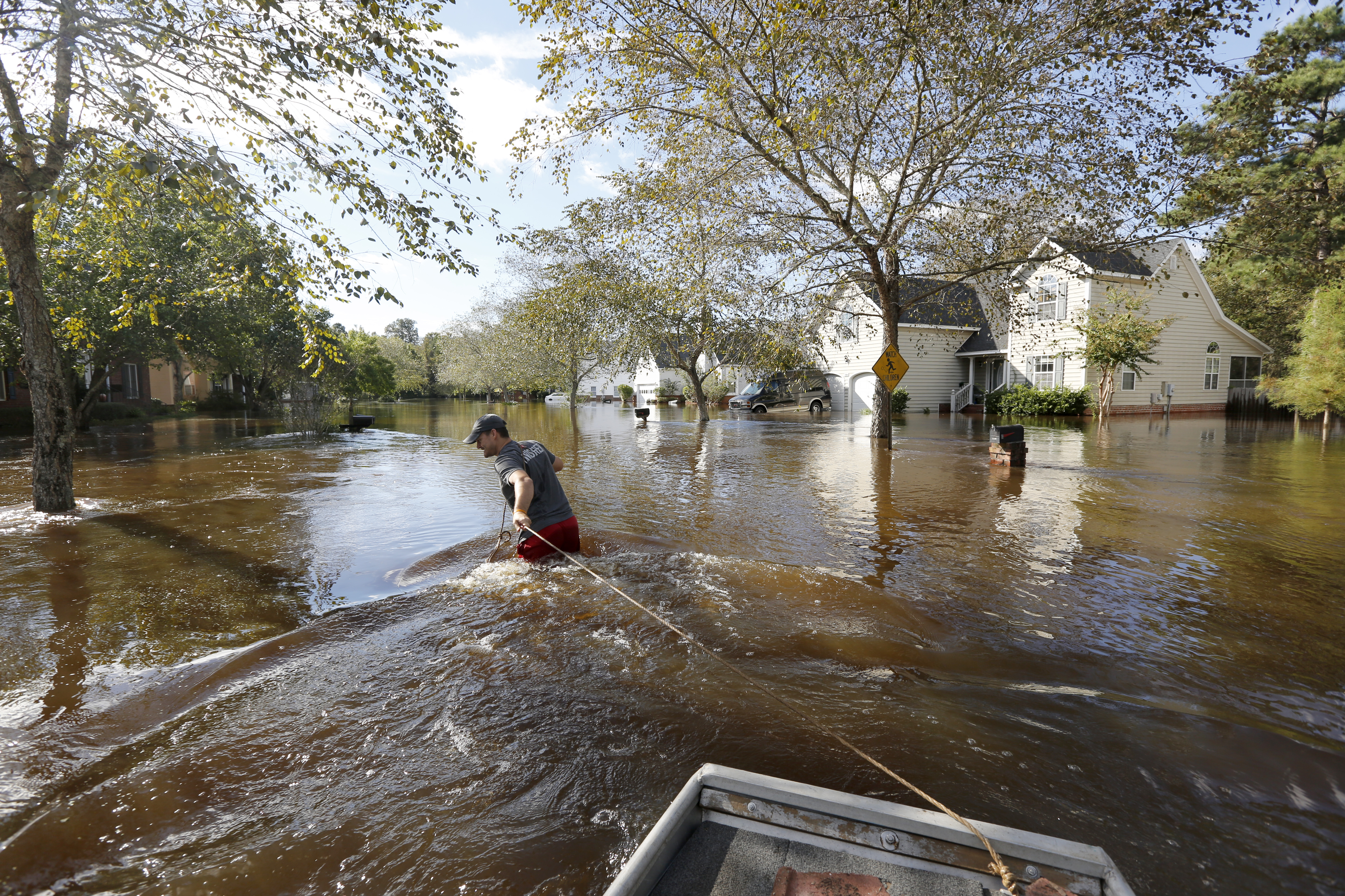 Ethan Abbott pulls his boat down Mayfield St. to help a friend get personal items out of the house in the Ashborough subdivision near Summerville, S.C., Oct. 6, 2015.
