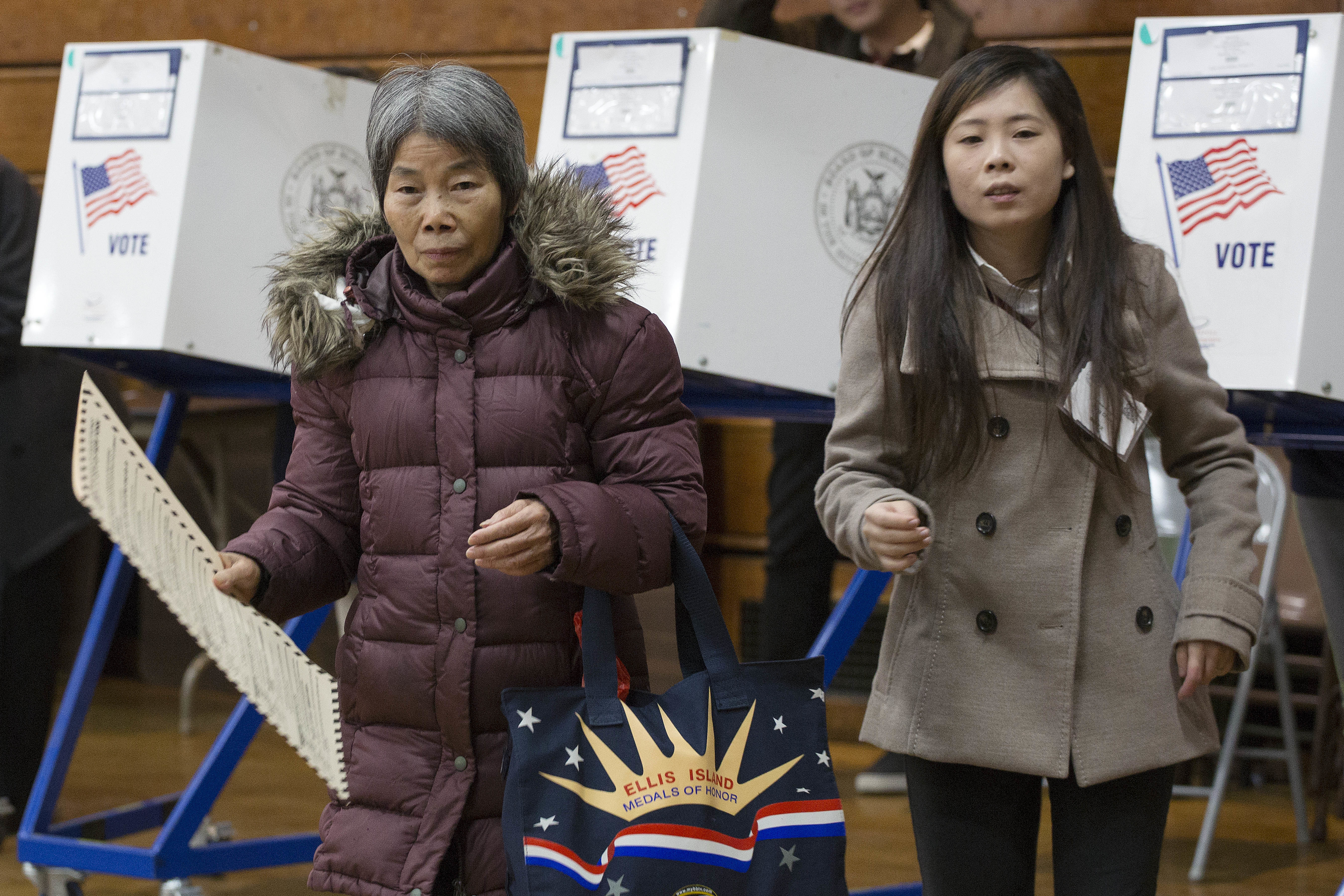 A voter, left, carries her ballot, while being assisted by interpreter Ping Chan, Nov. 8, 2016, in the Sunset Park neighborhood in the Brooklyn borough of New York.