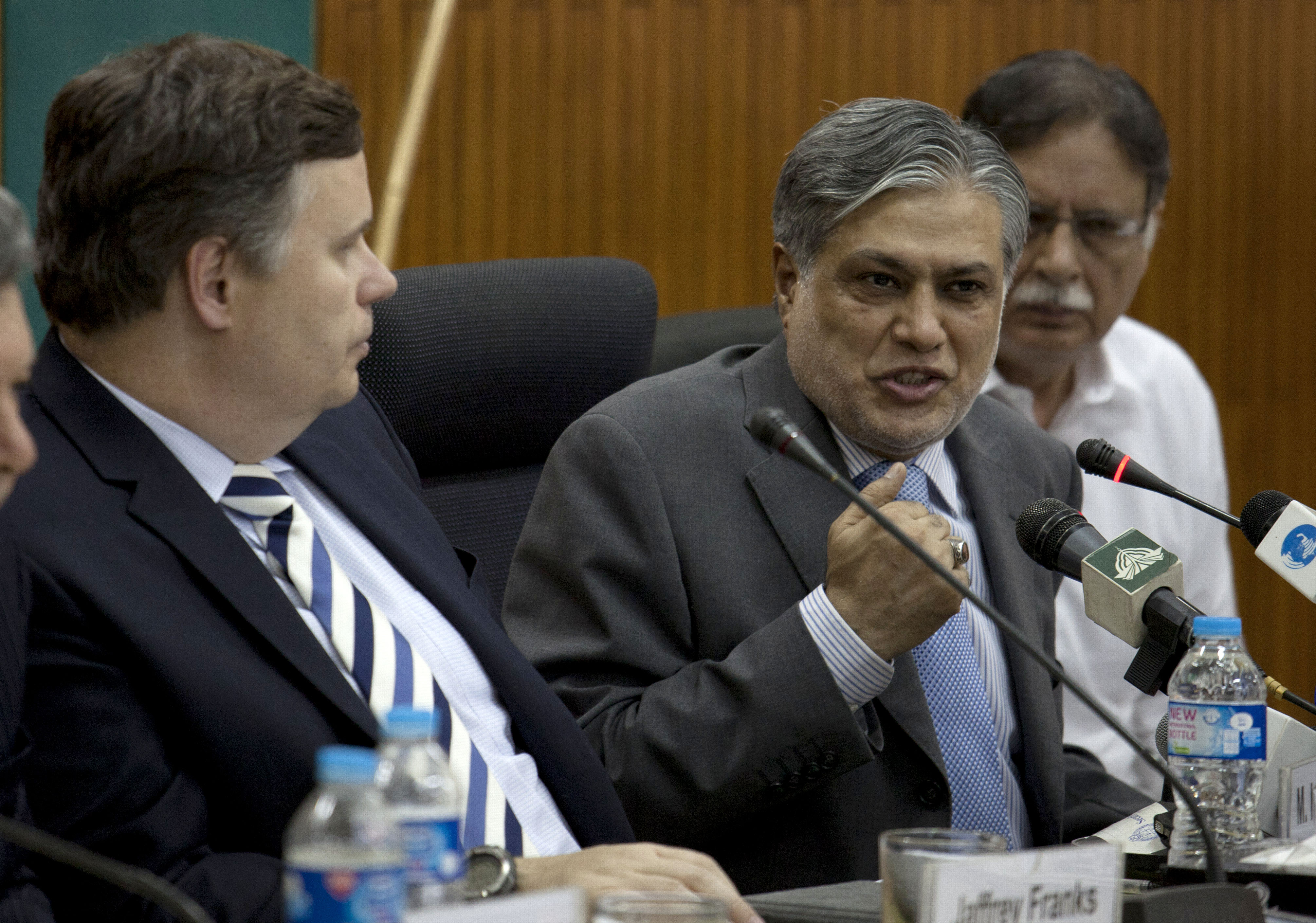 FILE - Then-Pakistani Finance Minister Muhammad Ishaq Dar, center, addresses a news conference with Jeffrey Franks, left, who then was the IMF mission chief for Pakistan, at the finance ministry in Islamabad, Pakistan, July 4, 2013. At the time, Paki...