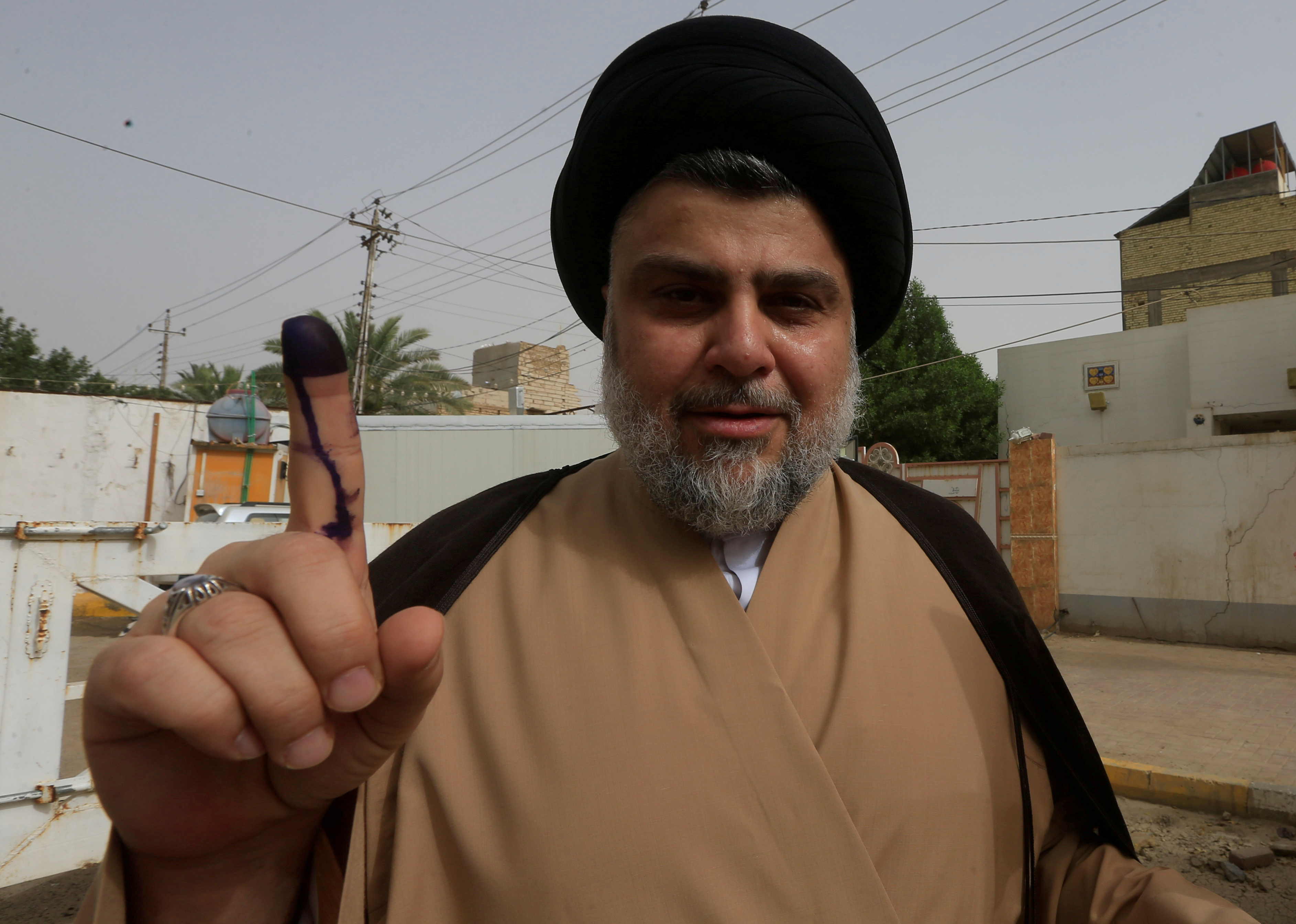 FILE - Iraqi Shi'ite cleric Moqtada al-Sadr shows his ink-stained finger after casting his vote at a polling station during the parliamentary election in Najaf, Iraq, May 12, 2018.