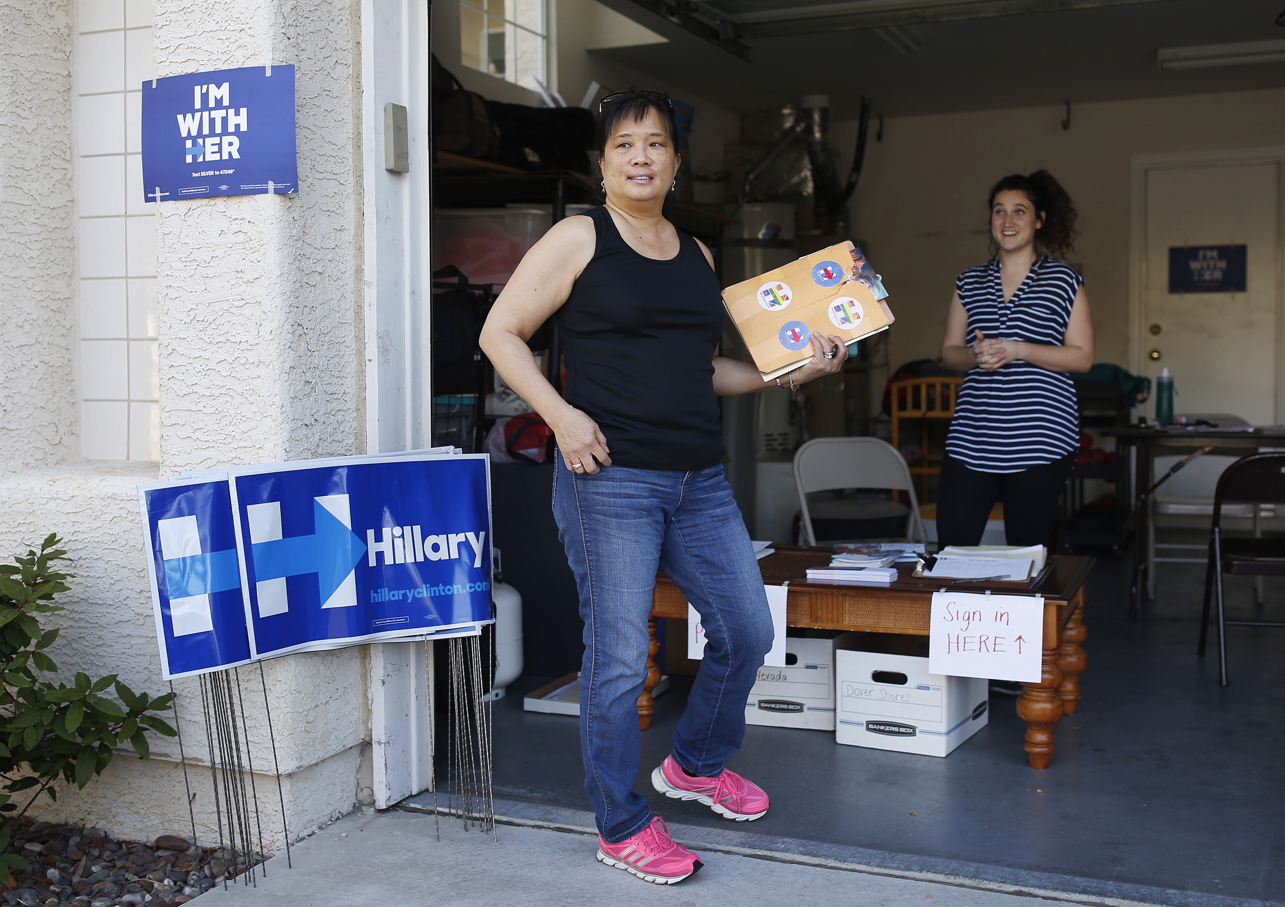 Cynthia Ameli, center, a Chinese-American, picks up materials from Sarah Gibson before heading out to canvass for presidential candidate Hillary Clinton in Las Vegas, Feb. 12, 2016.