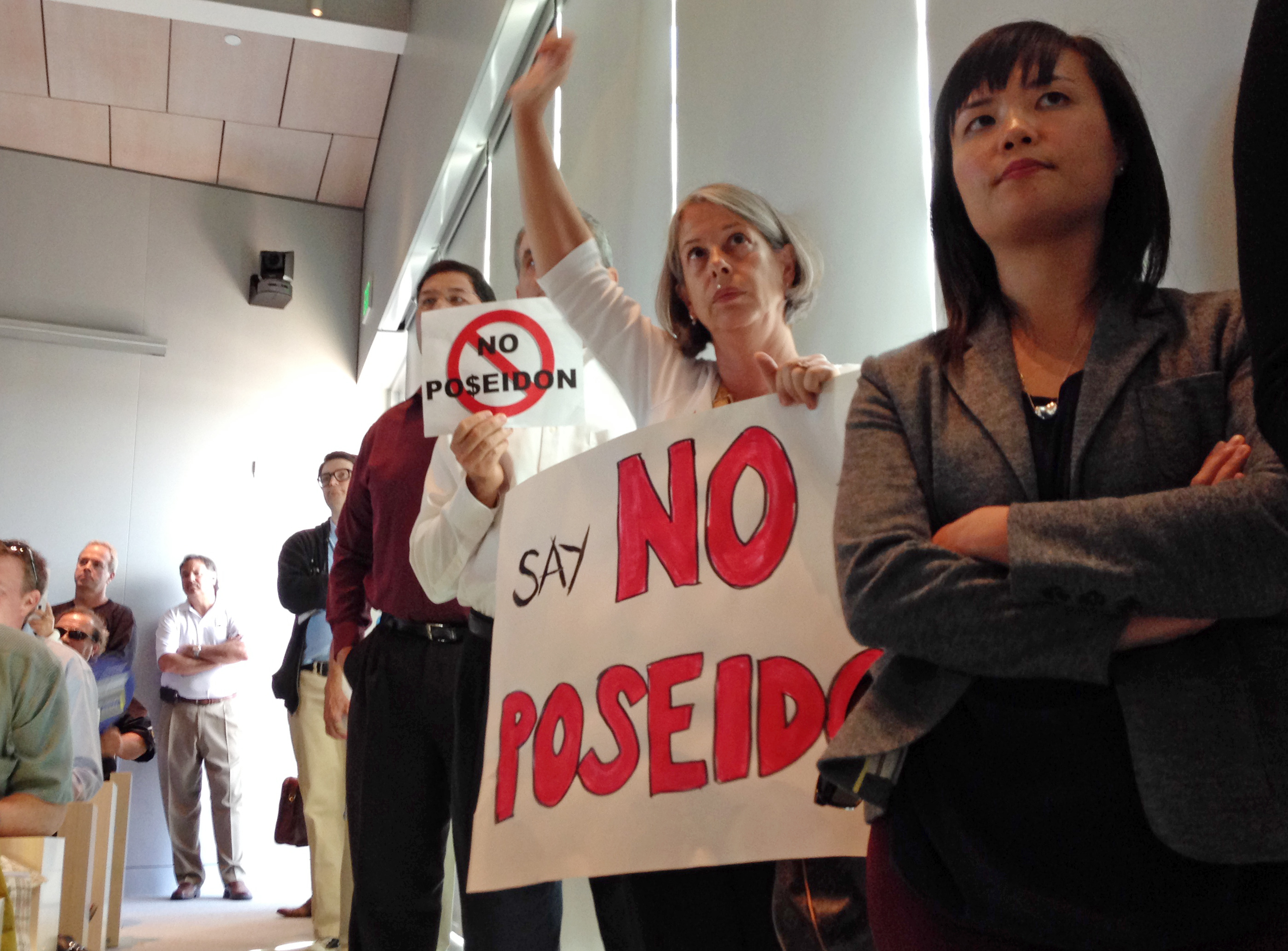 FILE - Scores of supporters and critics of a proposed $900 million desalination plant pack a meeting of the California Coastal Commission, in Huntington Beach, Calif., Nov. 13, 2013. Builder Poseidon Water hopes to get a permit to begin construction ...