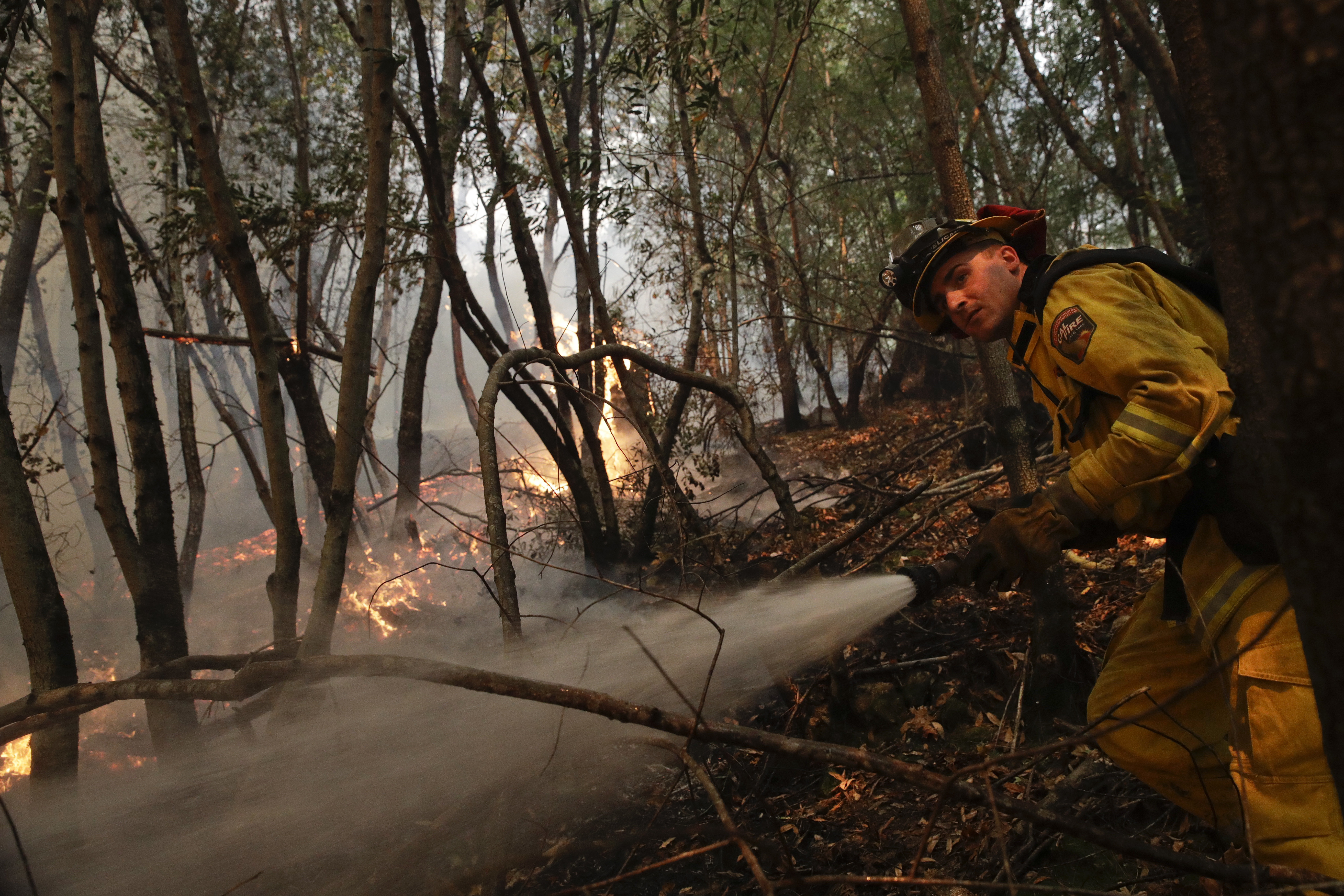 A firefighter puts out a hot spot from a wildfire, Oct. 12, 2017, near Calistoga, Calif. Officials say progress is being made in some of the largest wildfires burning in Northern California but that the death toll is almost sure to surge.
