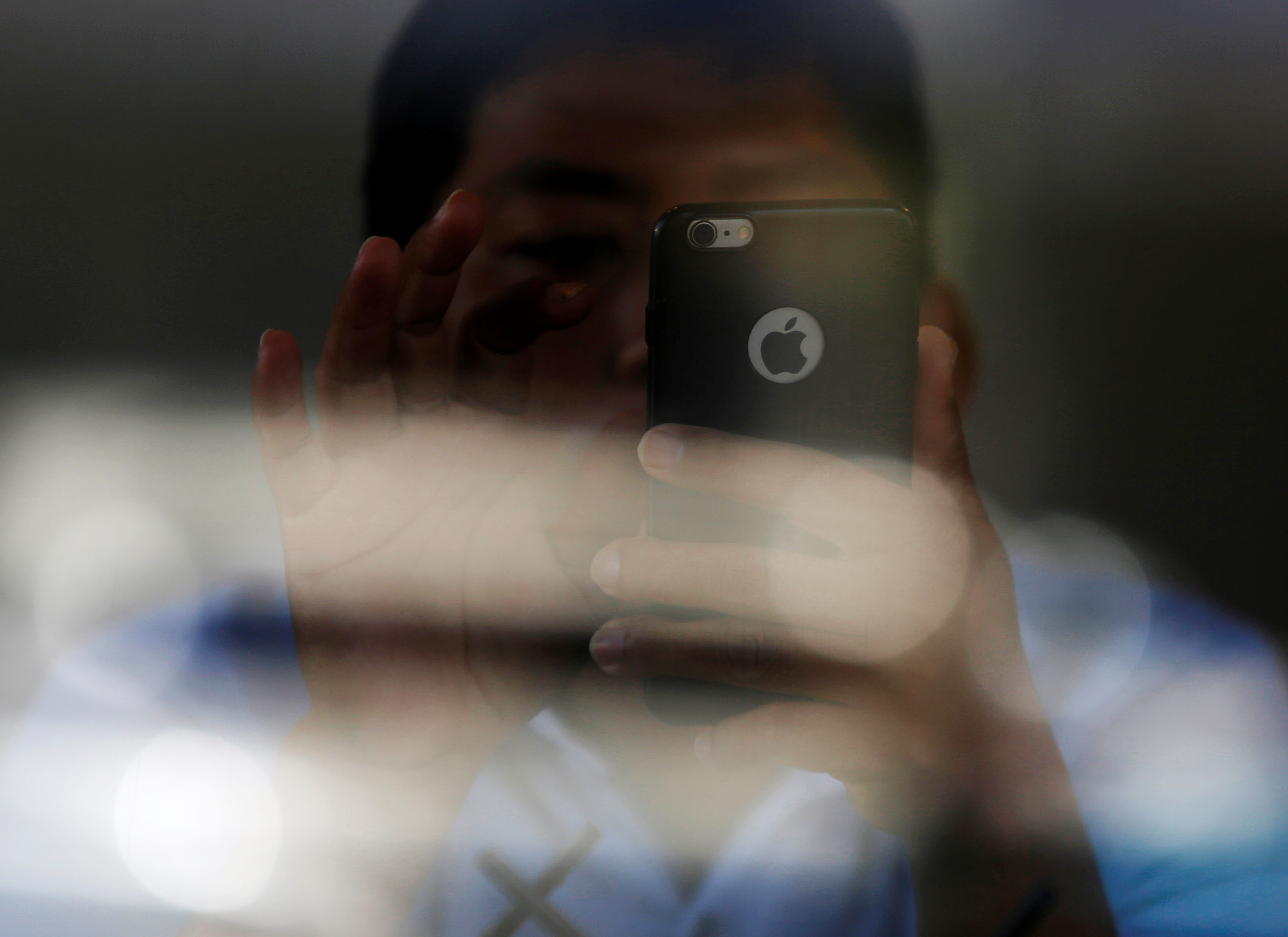 FILE - A man looks at his smartphone at a coffee shop in Phnom Penh, Cambodia, Oct. 23, 2018.