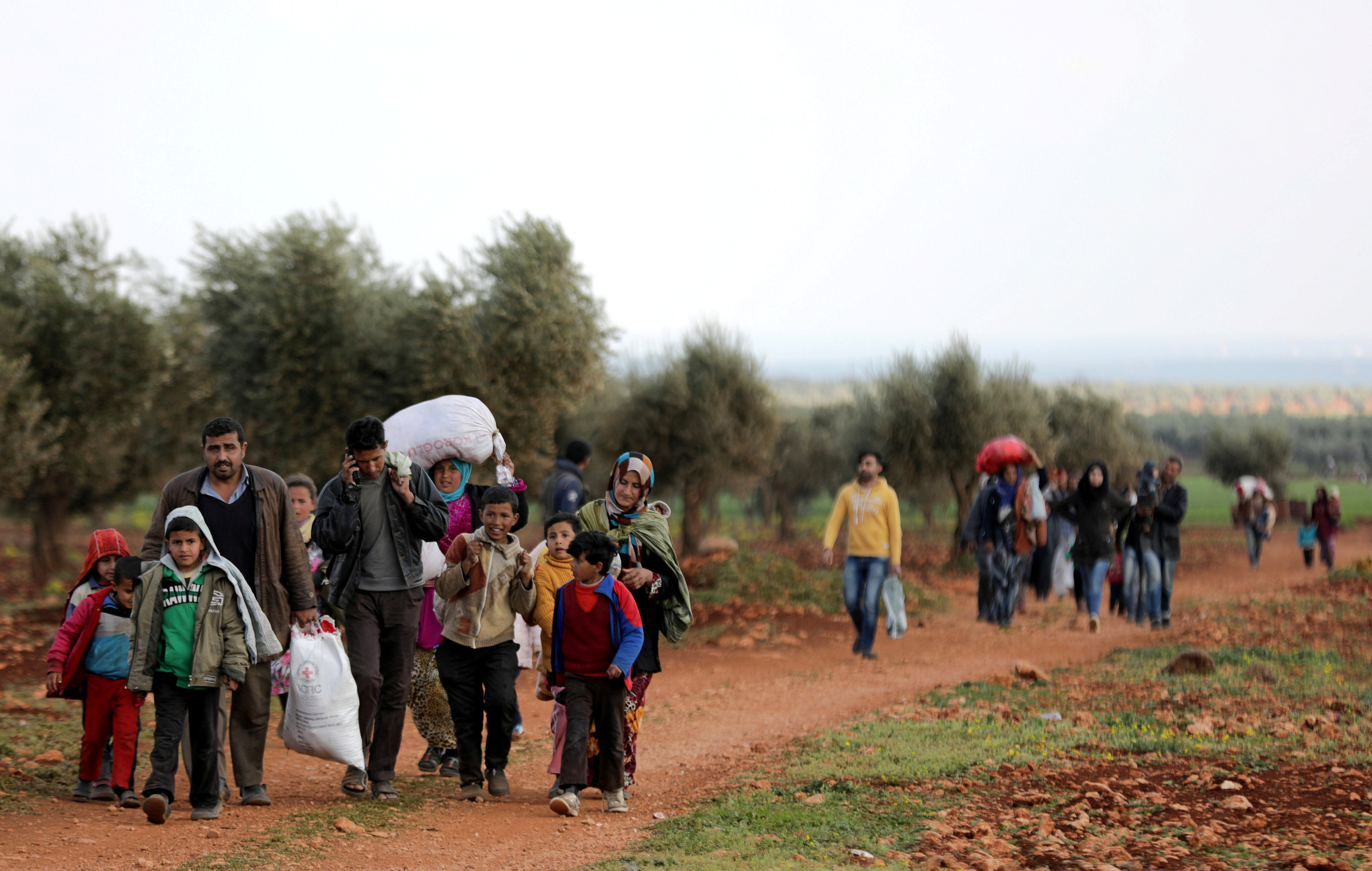 Internally displaced people walk with their belongings in the town of Inab, eastern Afrin, Syria, March 14, 2018.