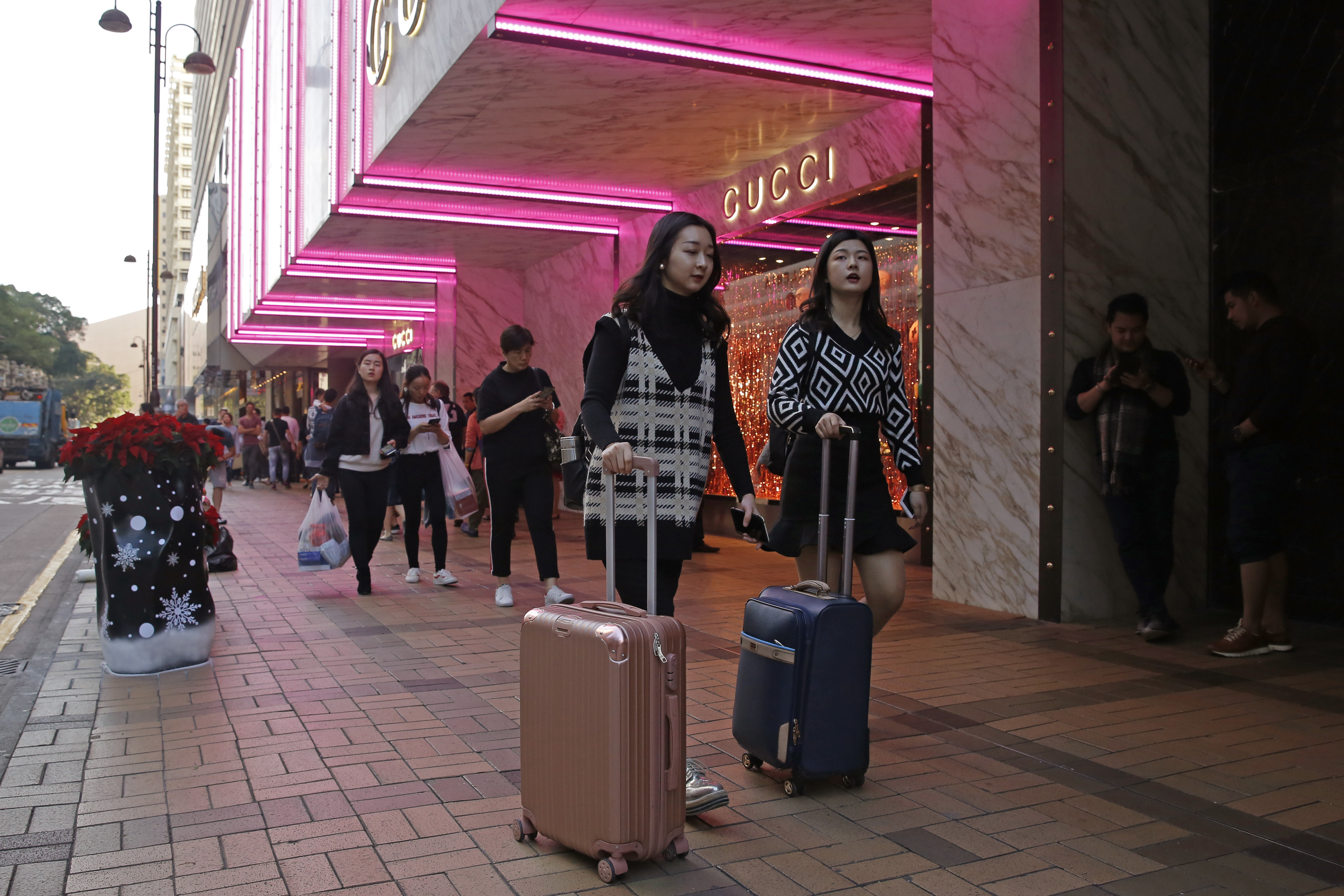 FILE - Chinese tourists walk on Canton Road, the one-stop-shop street of high-end brands in Hong Kong, Nov. 29, 2018.