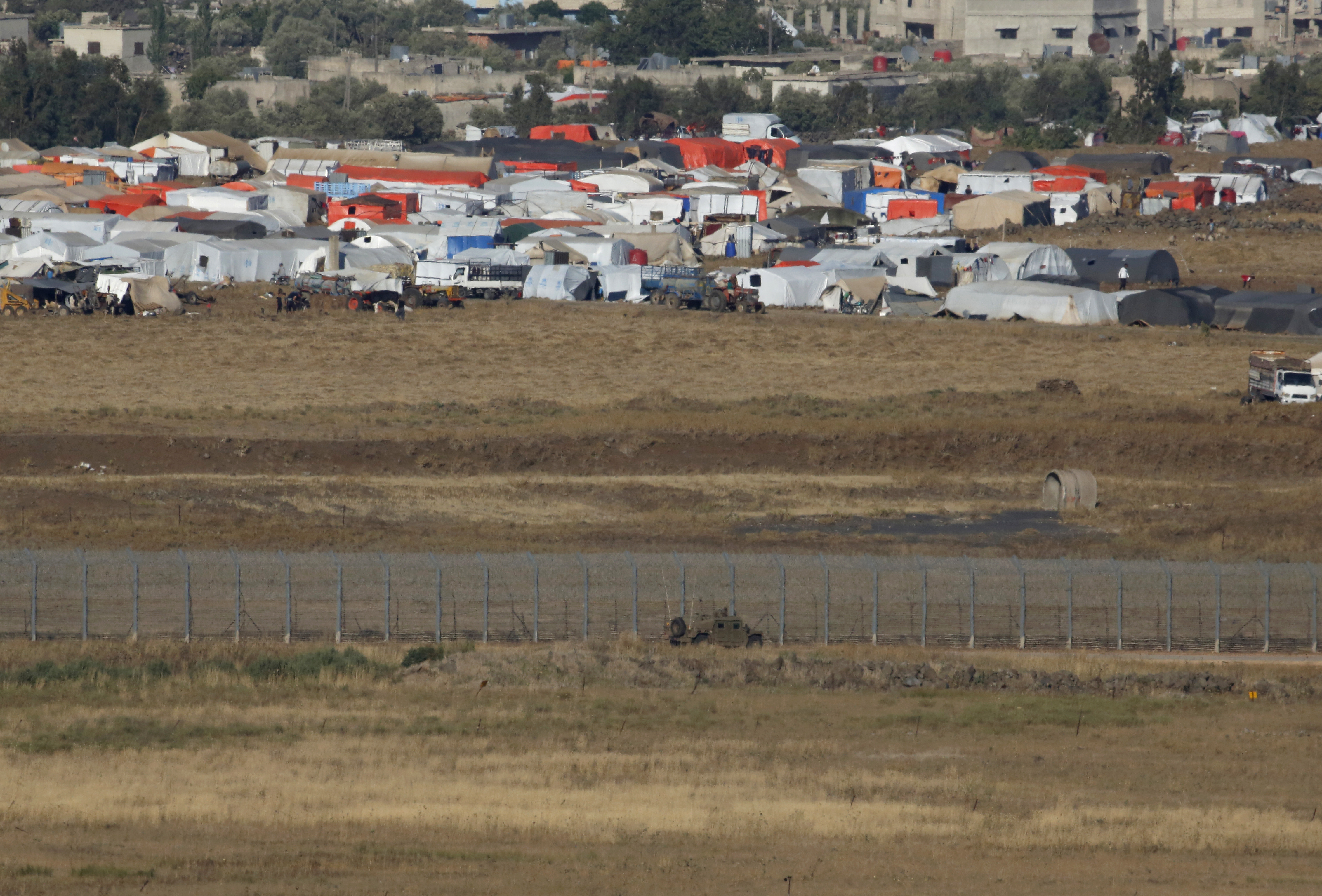 A picture taken on July 2, 2018 from the Israeli-annexed Syrian Golan Heights shows an Israeli army vehicle patrolling the border fence opposite a Syrian camp for the displaced near the village of Al-Rafeed in the southern Syrian province of Daraa.