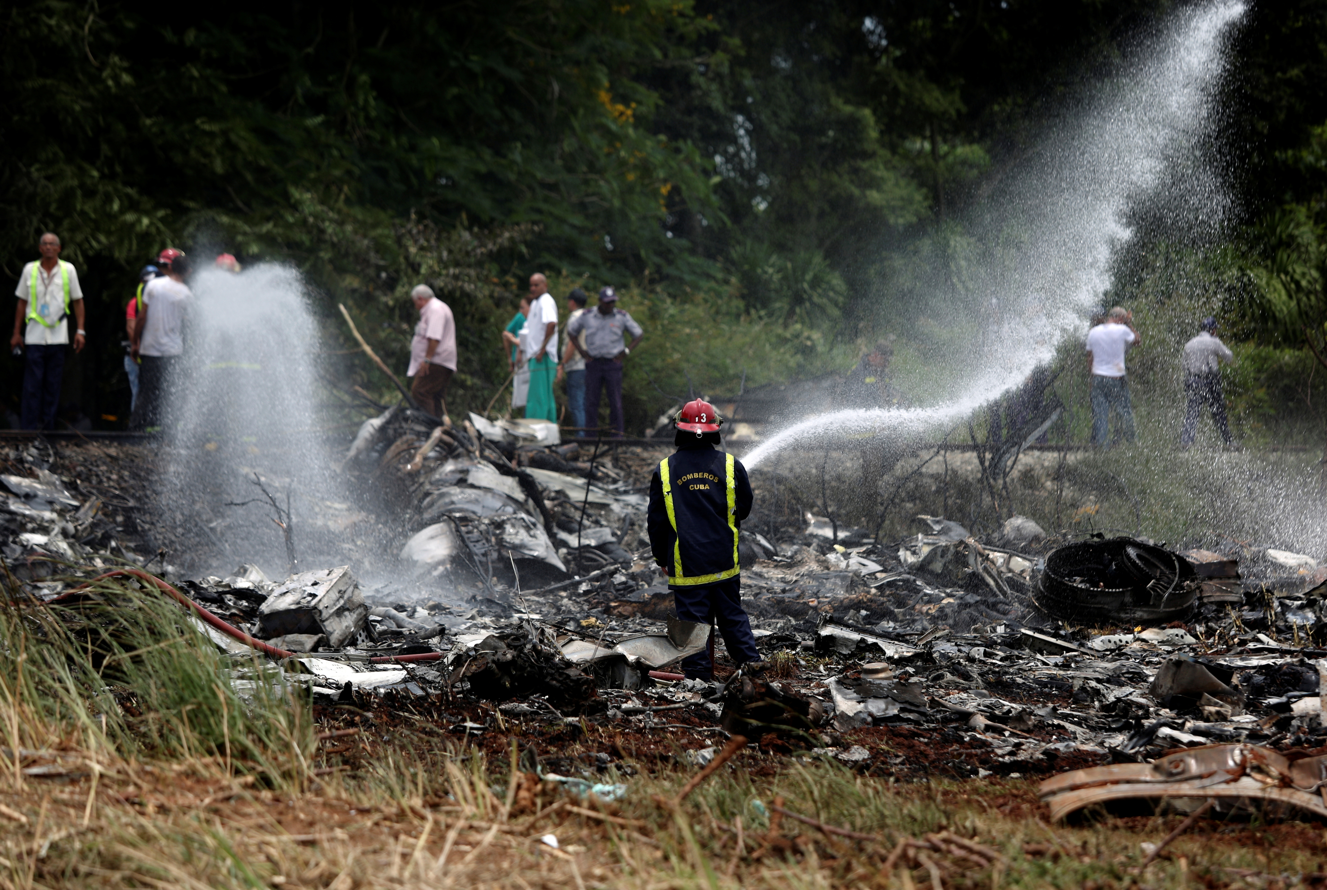 FILE - A firefighter works in the wreckage of a Boeing 737 plane that crashed in the agricultural area of Boyeros, south of Havana, shortly after taking off from Havana's main airport in Cuba, May 18, 2018.