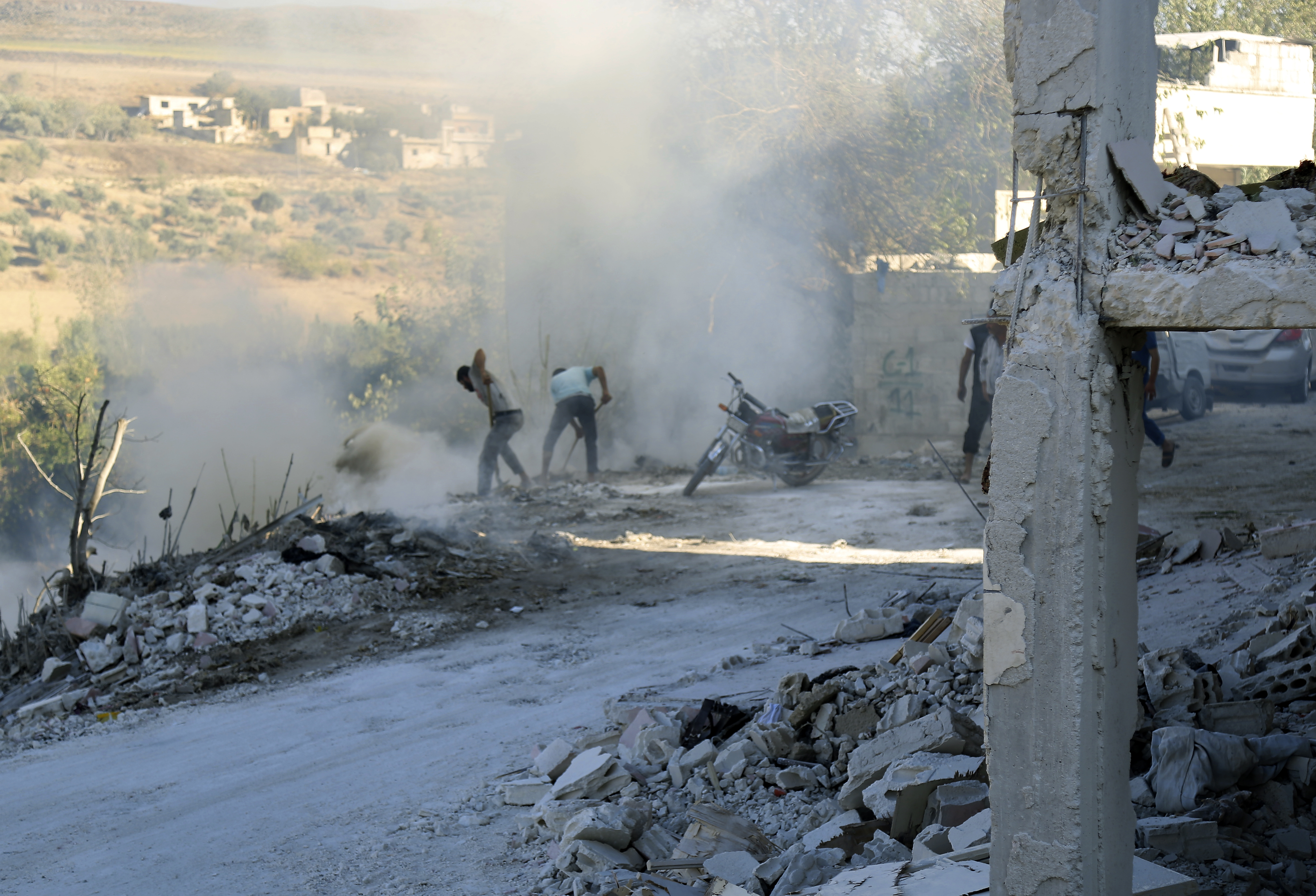 Syrians use dirt to put out a fire at the scene of a reported airstrike in the district of Jisr al-Shughur, in the Idlib province, Sept. 4, 2018.