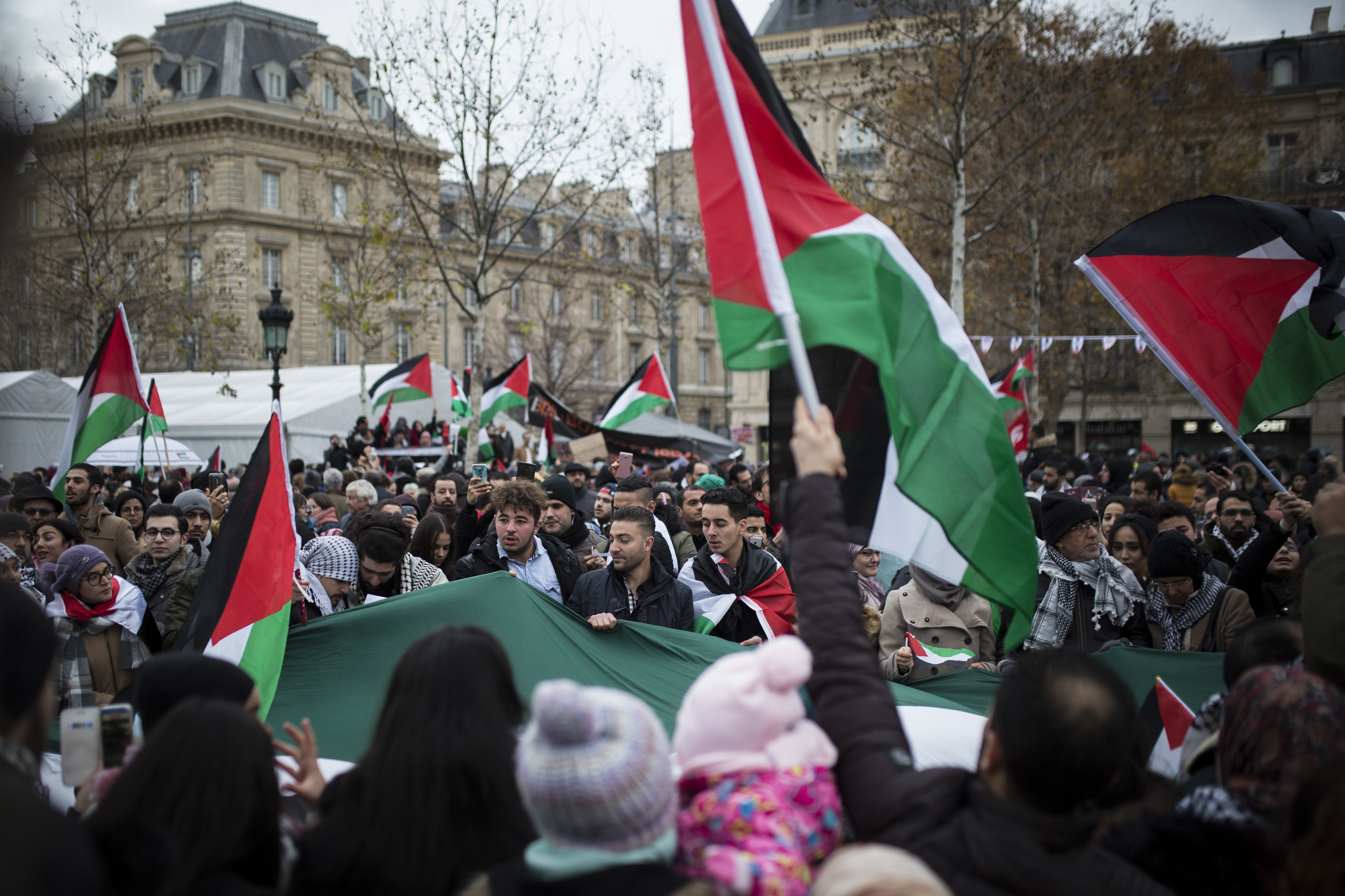 Demonstrators shout as they hold Palestinian flags during a protest against U.S. President Donald Trump's decision to recognize Jerusalem as Israel's capital, at Republique Square in Paris, France, Dec. 9, 2017.