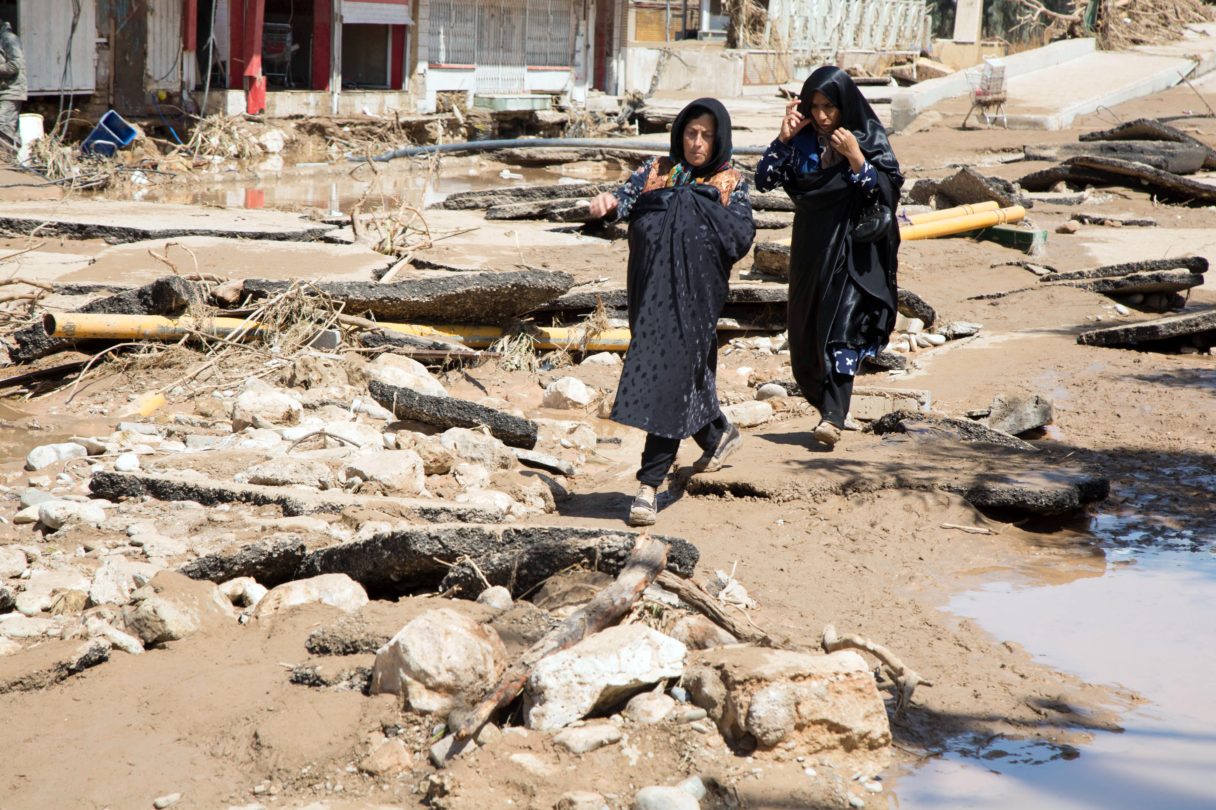 An Iranian woman walks through a flooded street in the city of Poldokhtar in the Lorestan province, April 02, 2019.
