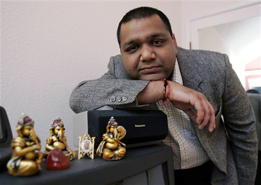 Gautam Aggarwal, a software engineer from India working for a Silicon Valley startup, poses with Indian god figures on his television set at his home in Mountain View, California.