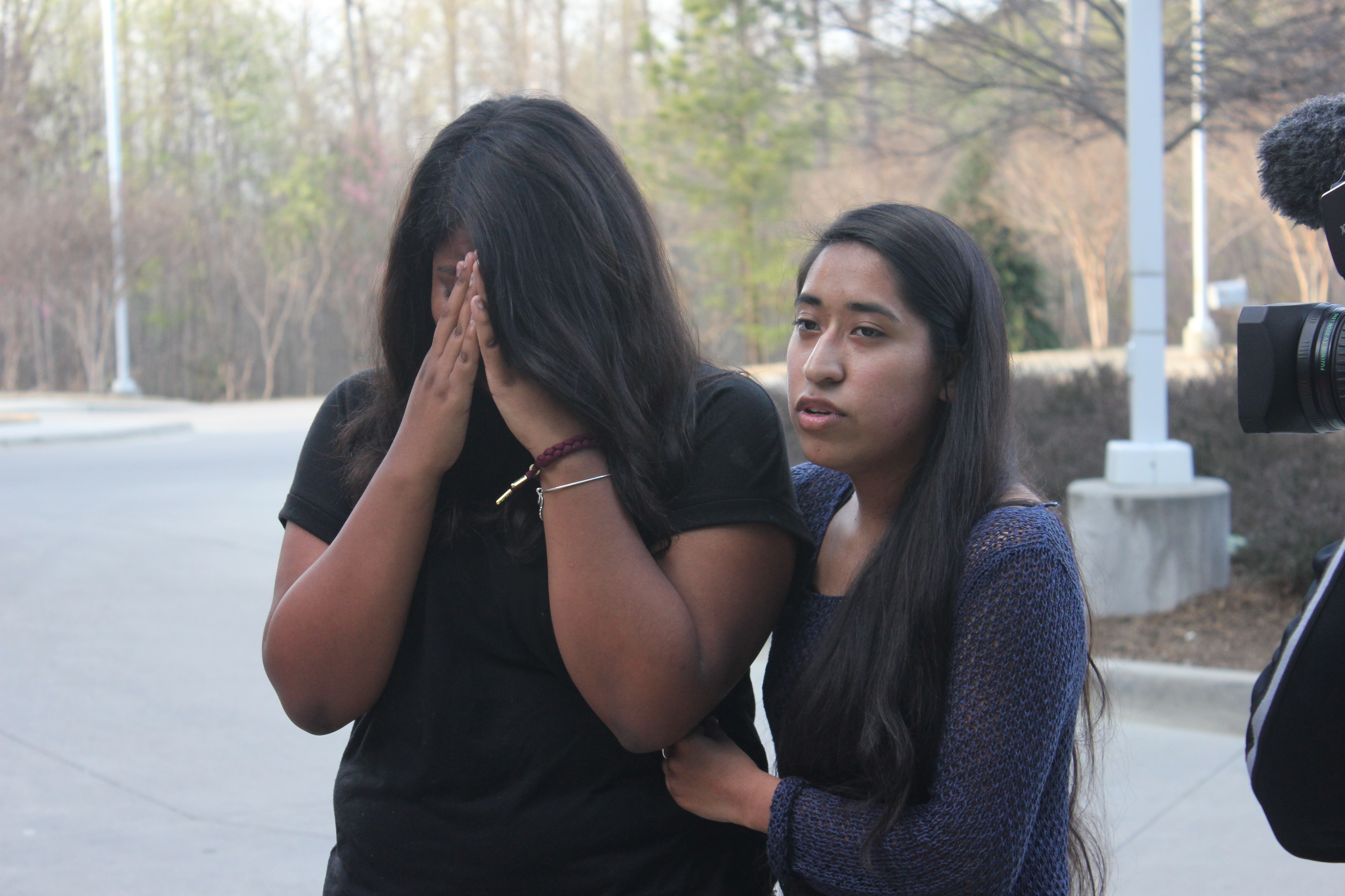 Edith Galvan, an undocumented immigrant and DACA recipient, offers support to Alisha Marcial during a vigil in honor of Marcial's father. The father of seven U.S.-born children is detained at a county jail in Raleigh, North Carolina. (Photo: A. Bar...