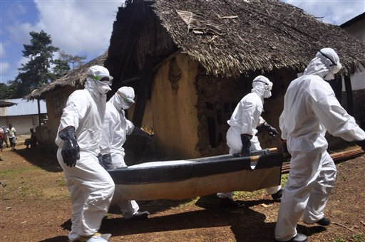 Health workers carry the body of a woman suspected of contracting the Ebola virus in Bomi county situated on the outskirts of Monrovia, Liberia, Monday, Oct. 20, 2014.  Liberian President Ellen Johnson Sirleaf said Ebola has killed more than 2,000 pe...
