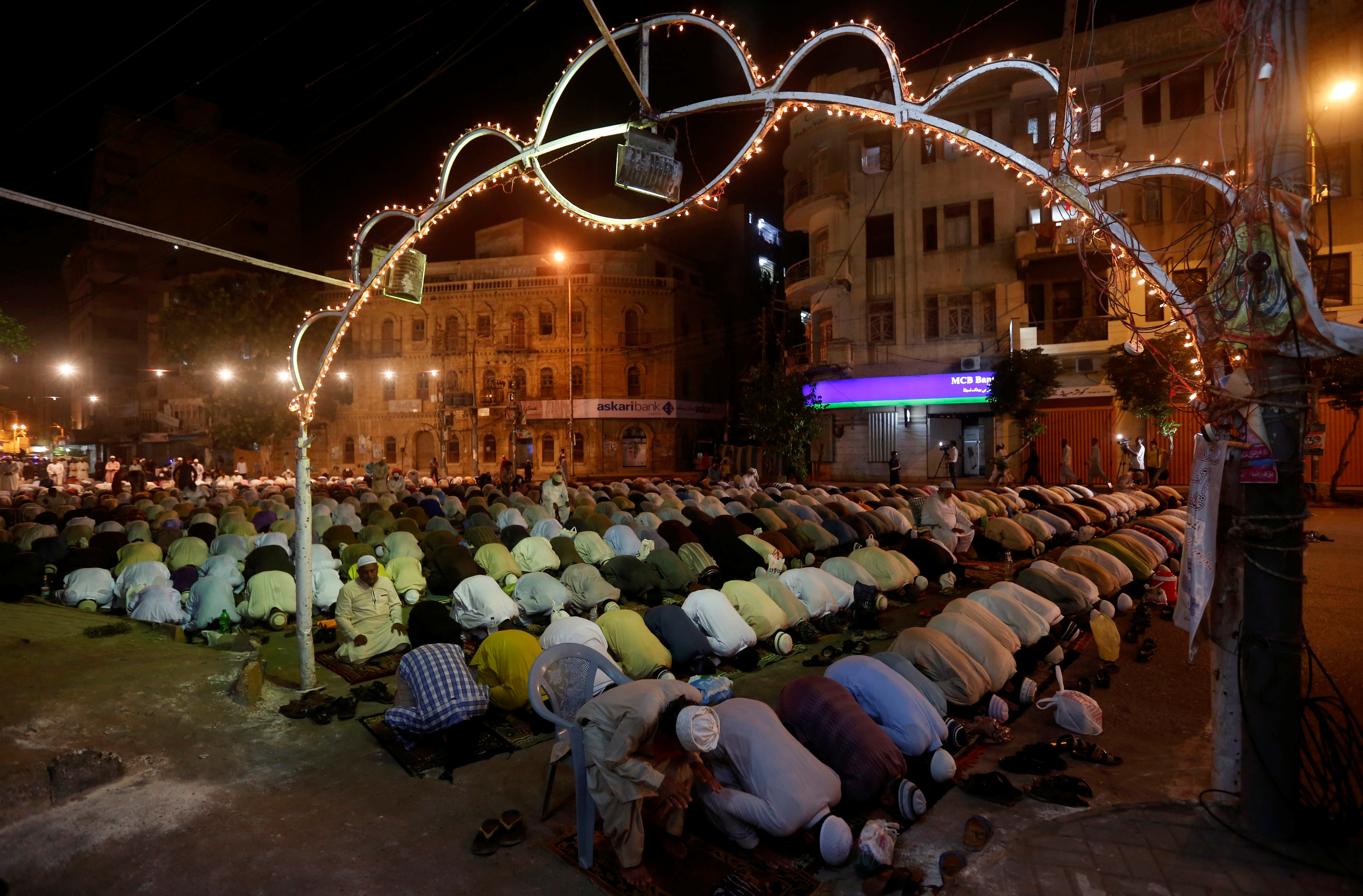 Men attend an evening mass prayer session called tarawih along a road to mark the fasting month of Ramadan in Karachi, Pakistan, May 27, 2017.