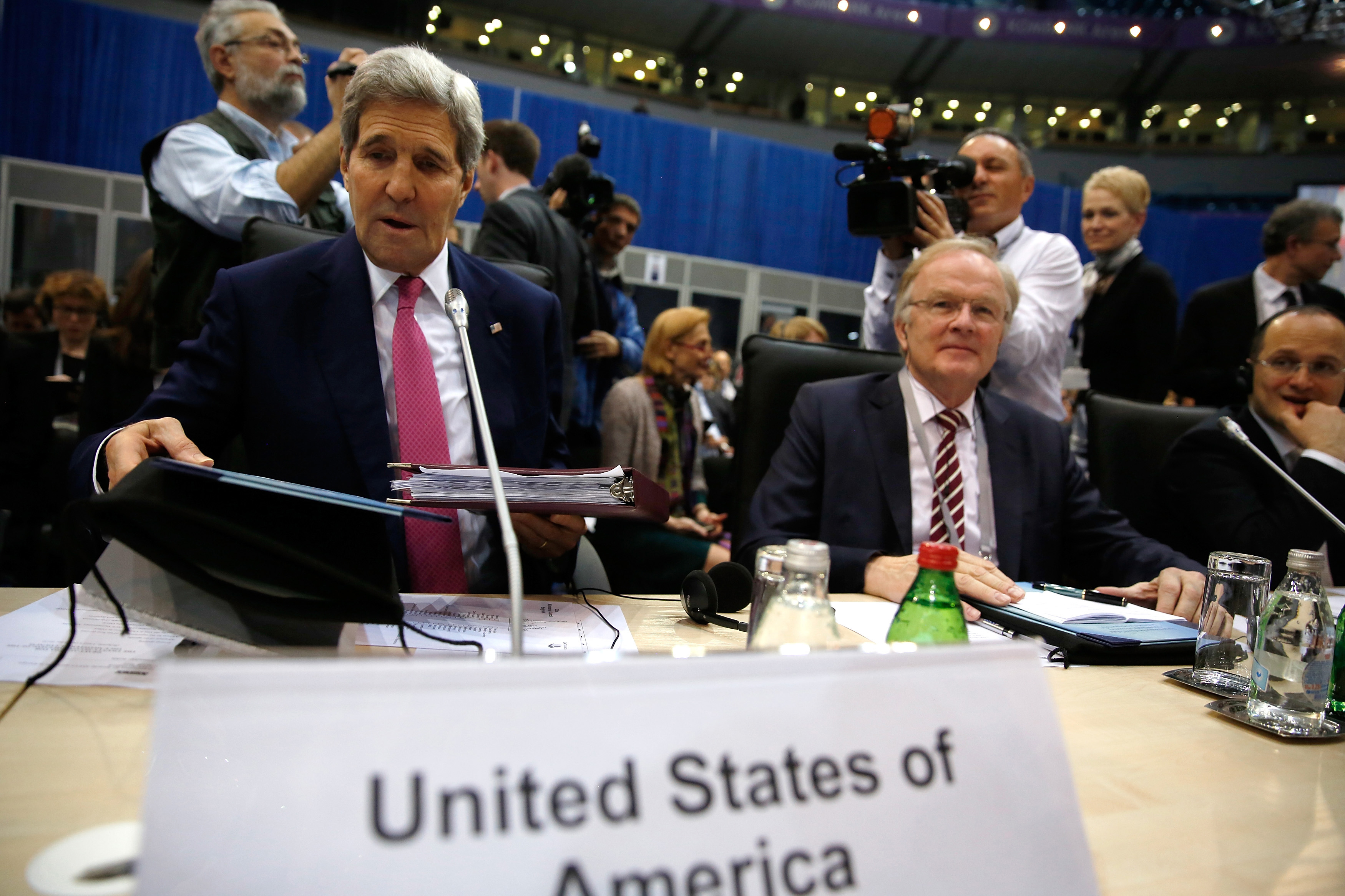 U.S. Secretary of State John Kerry, left, takes his seat to participate in the Organization for Security and Cooperation in Europe (OSCE) ministerial council meeting in Belgrade, Serbia Thursday, Dec. 3, 2015.