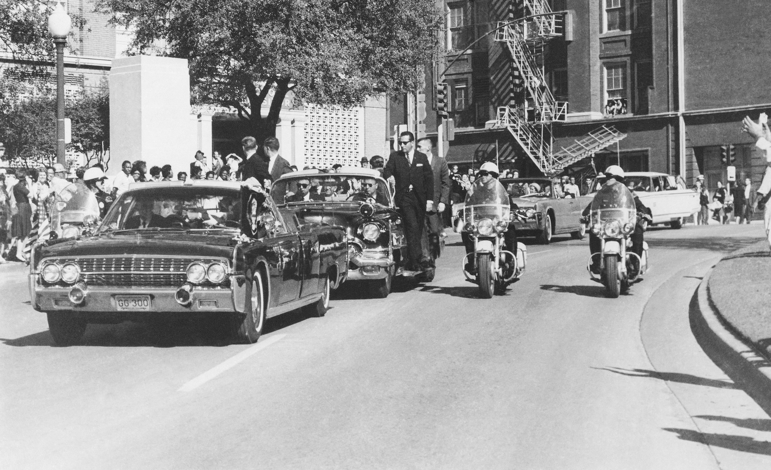 Seen through the limousine's windshield as it proceeds along Elm Street past the Texas School Book Depository, President John F. Kennedy appears to raise his hand toward his head within seconds of being fatally shot in Dallas, Nov 22, 1963.