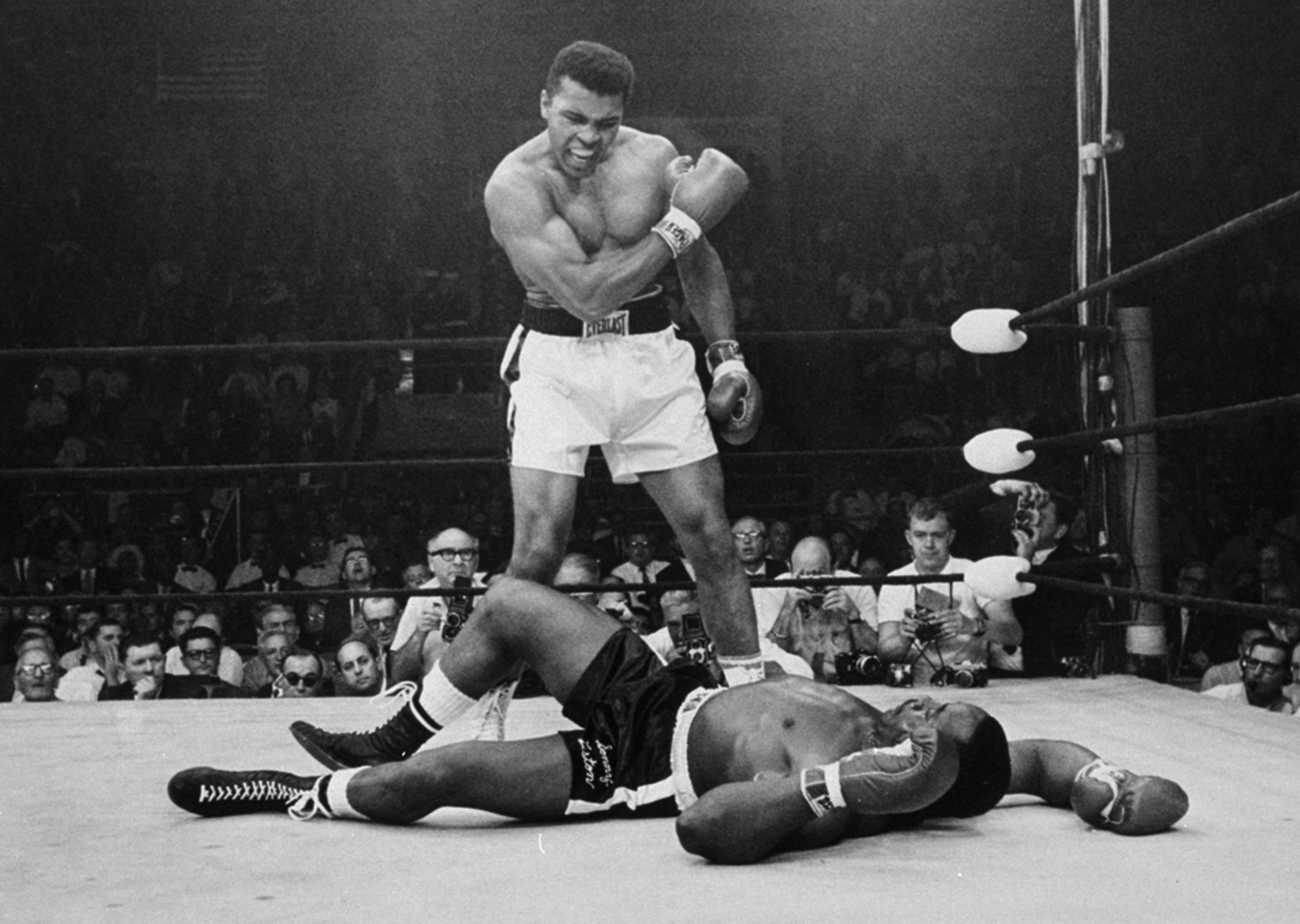 FILE - Heavyweight champion Muhammad Ali stands over fallen challenger Sonny Liston, shouting and gesturing shortly after dropping Liston with a short hard right to the jaw, in Lewiston, Maine, May 25, 1965.