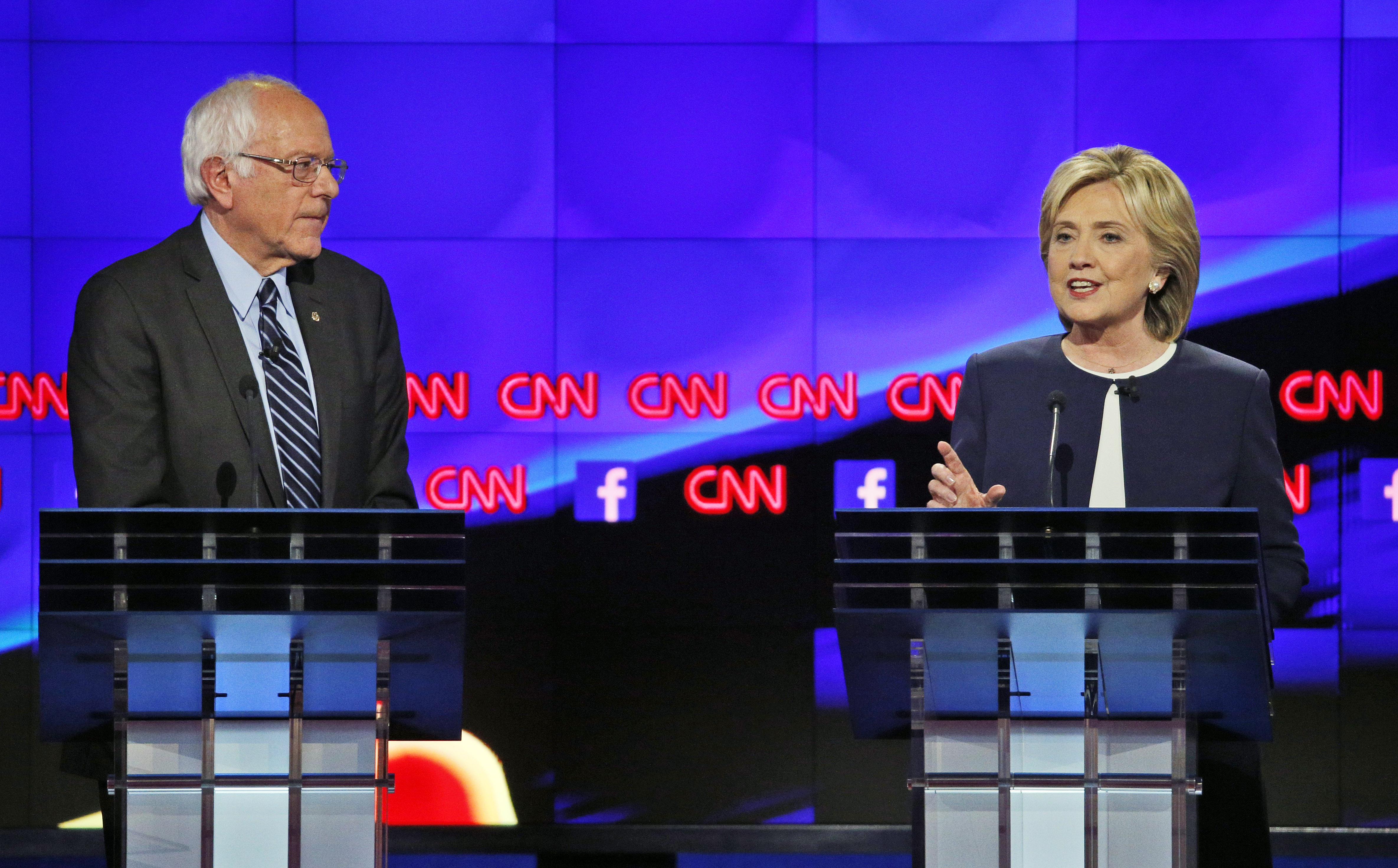 Former Secretary of State Hillary Clinton talks as Sen. Bernie Sanders of Vermont listens during the CNN Democratic presidential debate in Las Vegas, Oct. 13, 2015.