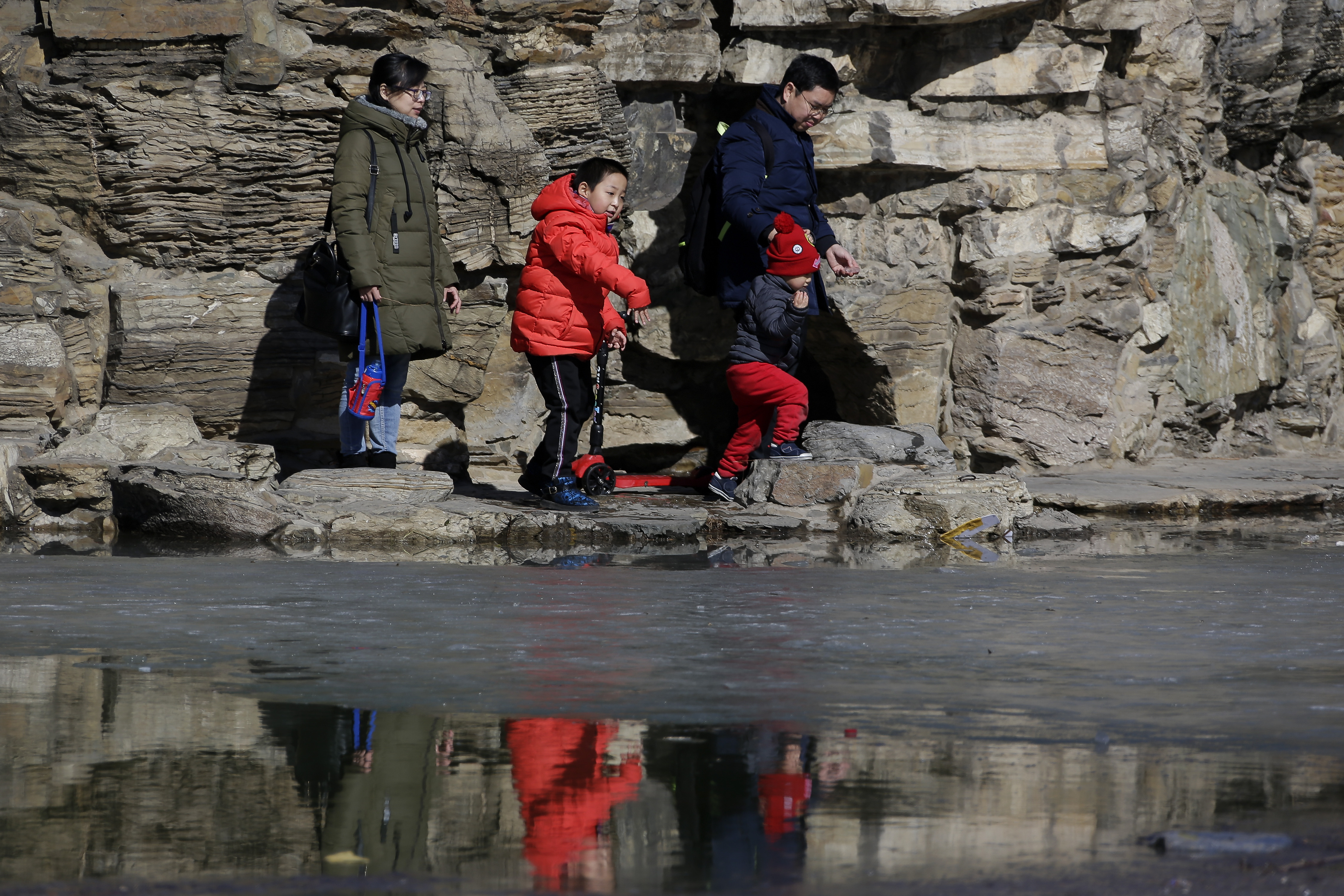 In this Feb. 17, 2019, photo, a couple bring their children tour a park in Beijing. Facing a future demographic crisis and aging society, China's leaders are desperately seeking to persuade couples to have more children.