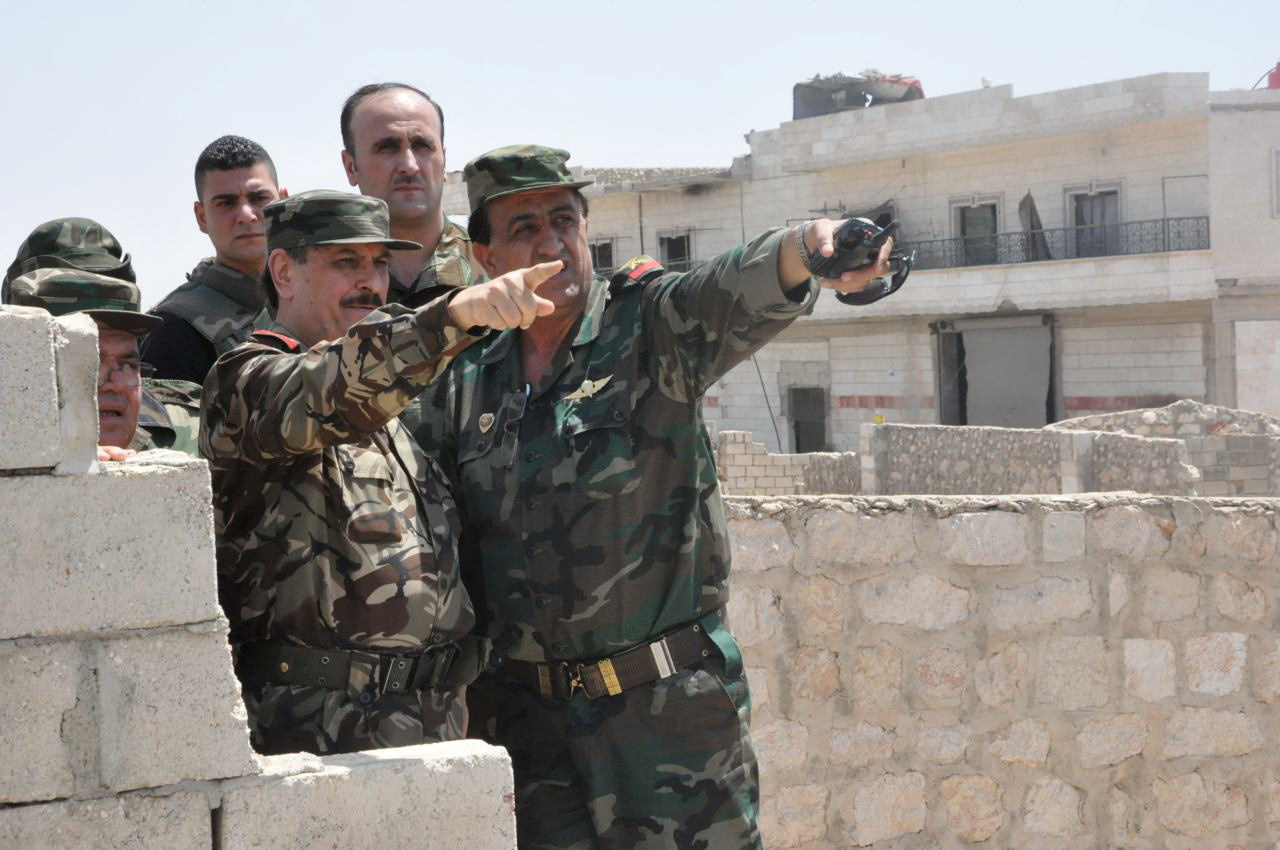 Syrian Minister of Defense, Fahd Jassem al-Freij, center, gestures during a visit to Syrian regime soldiers in Aleppo, Syria. Aug. 9, 2016.
