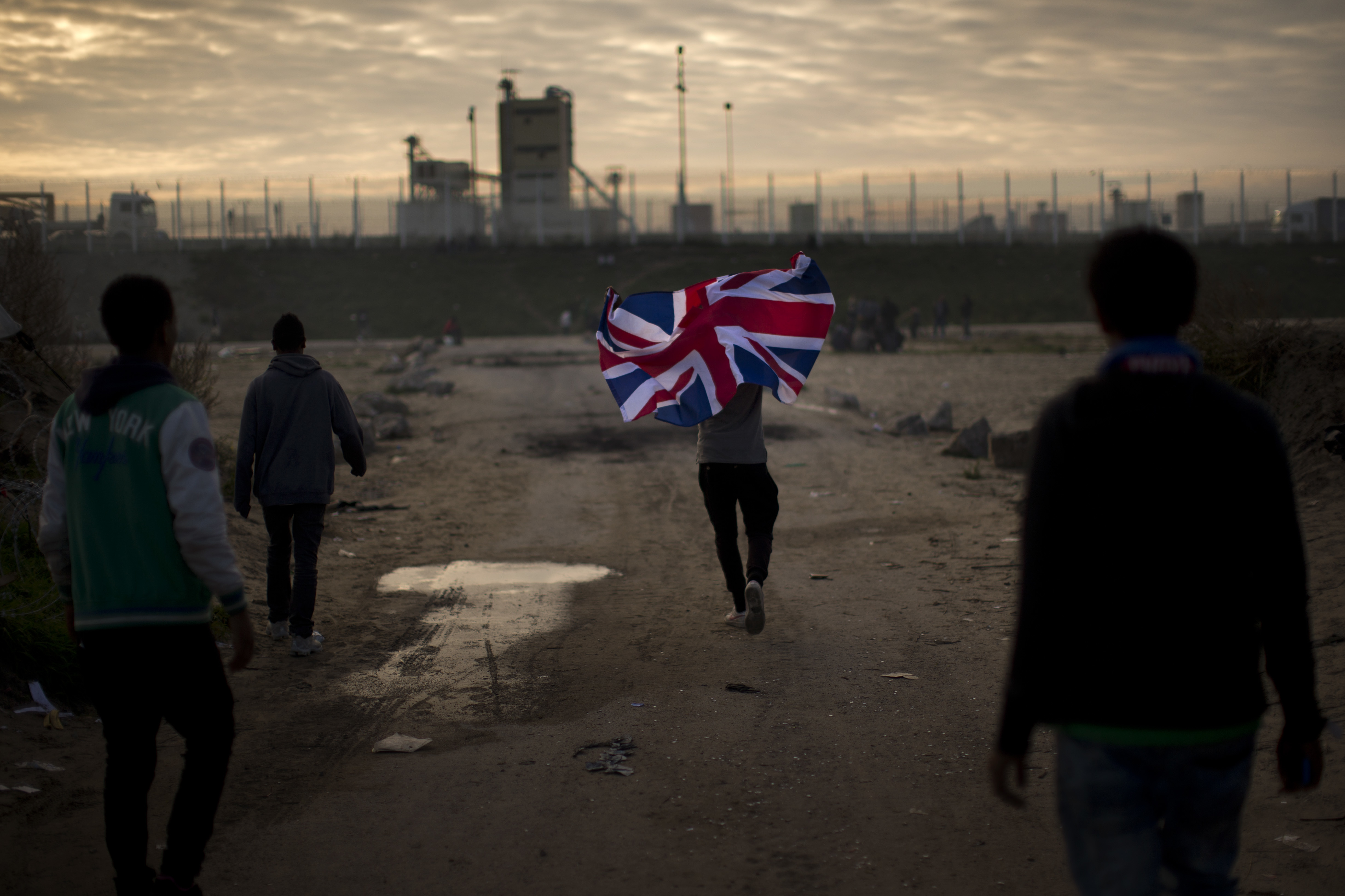 """A man runs with a British flag inside a makeshift camp known as """"the jungle"""" near Calais, northern France, Oct. 25, 2016."""