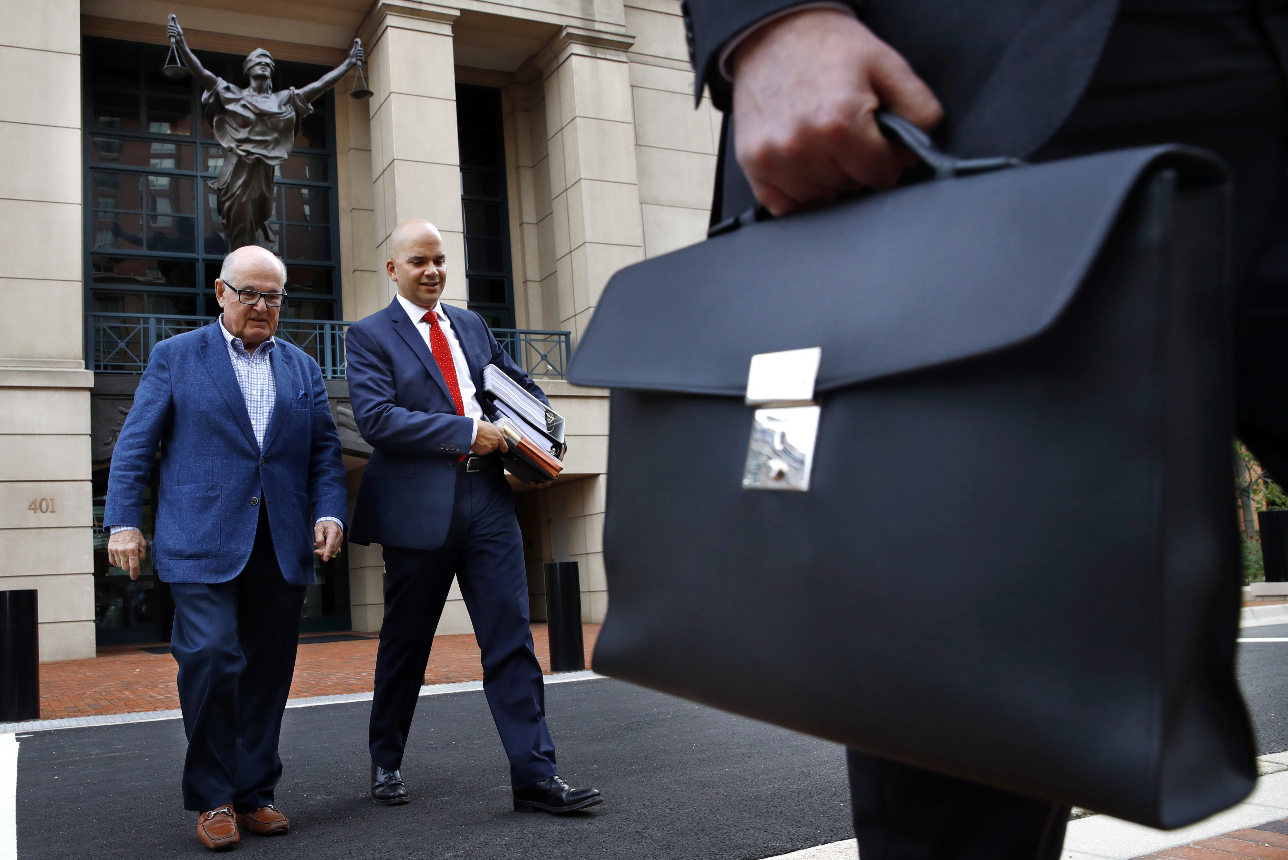 Jay Nanavati, second from left, one of the lawyers for former Donald Trump campaign chairman Paul Manafort, leaves federal court after attending the Manafort trial in Alexandria, Virginia,  Aug. 7, 2018.