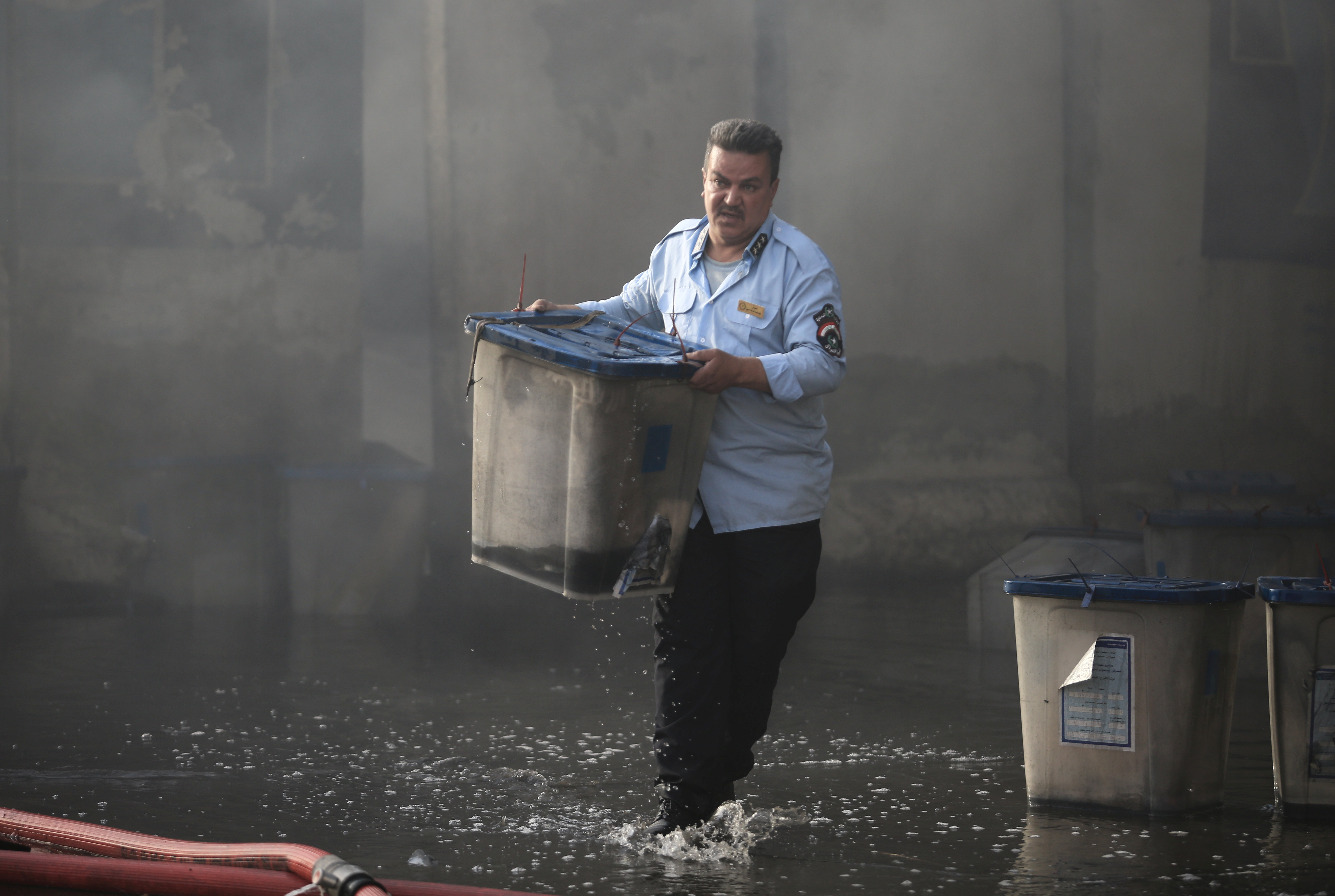 An official carries a ballot box after a fire at a storage site in Baghdad that houses the boxes from Iraq's May parliamentary election, Iraq, June 10, 2018.