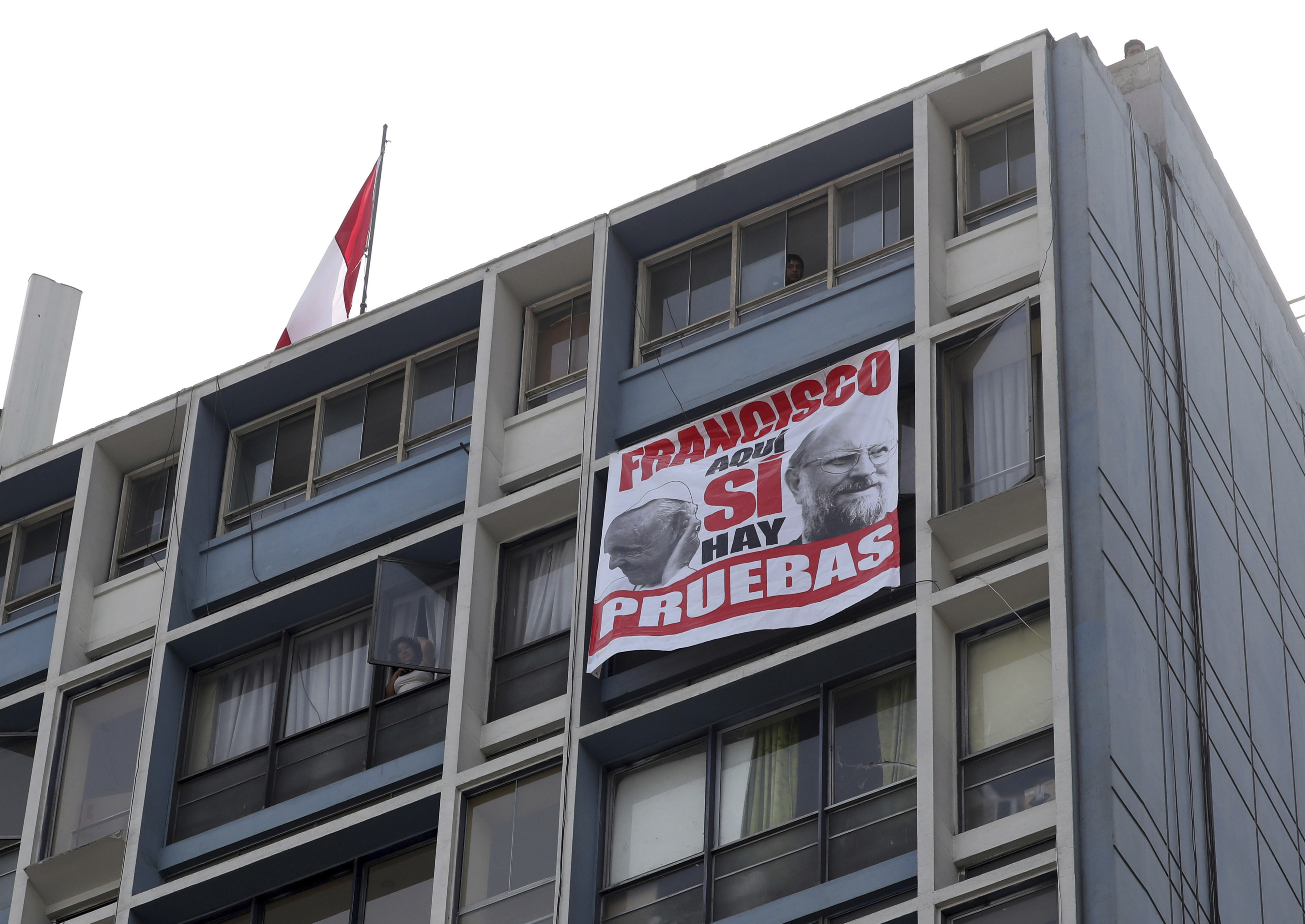 """A protest banner that shows images of Pope Francis and Cardinal Sean O'Malley with a message that reads in Spanish: """"Francisco, here we do have proof"""", hangs from a building located outside the Shrine of Our Lord of the Miracles, in Lima, Jan. 21, 20..."""