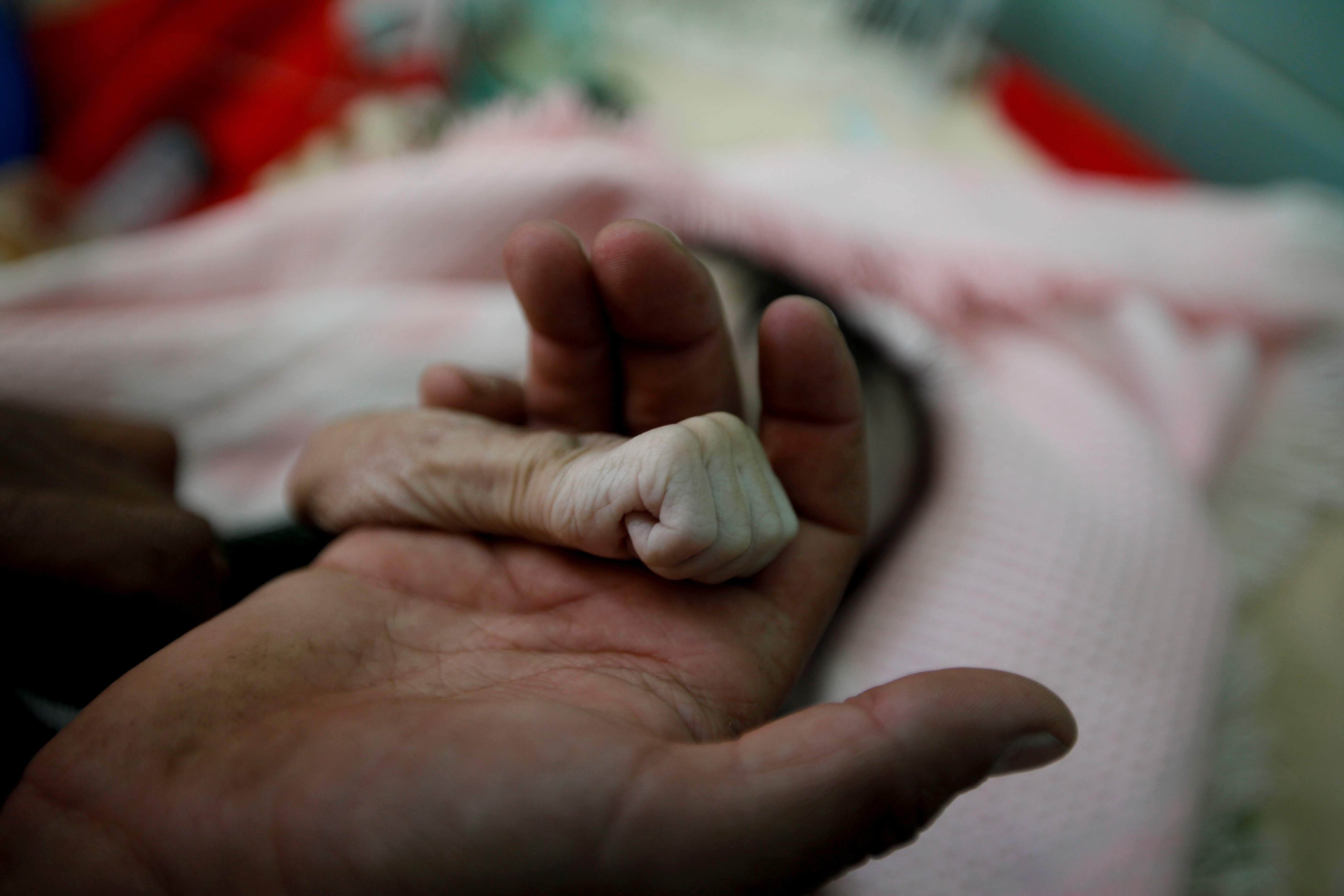 Saleh Hassan al-Faqeh holds the hand of his four-month-old daughter, Hajar, who died at the malnutrition ward of al-Sabeen hospital in Sanaa, Yemen, November 15, 2018.