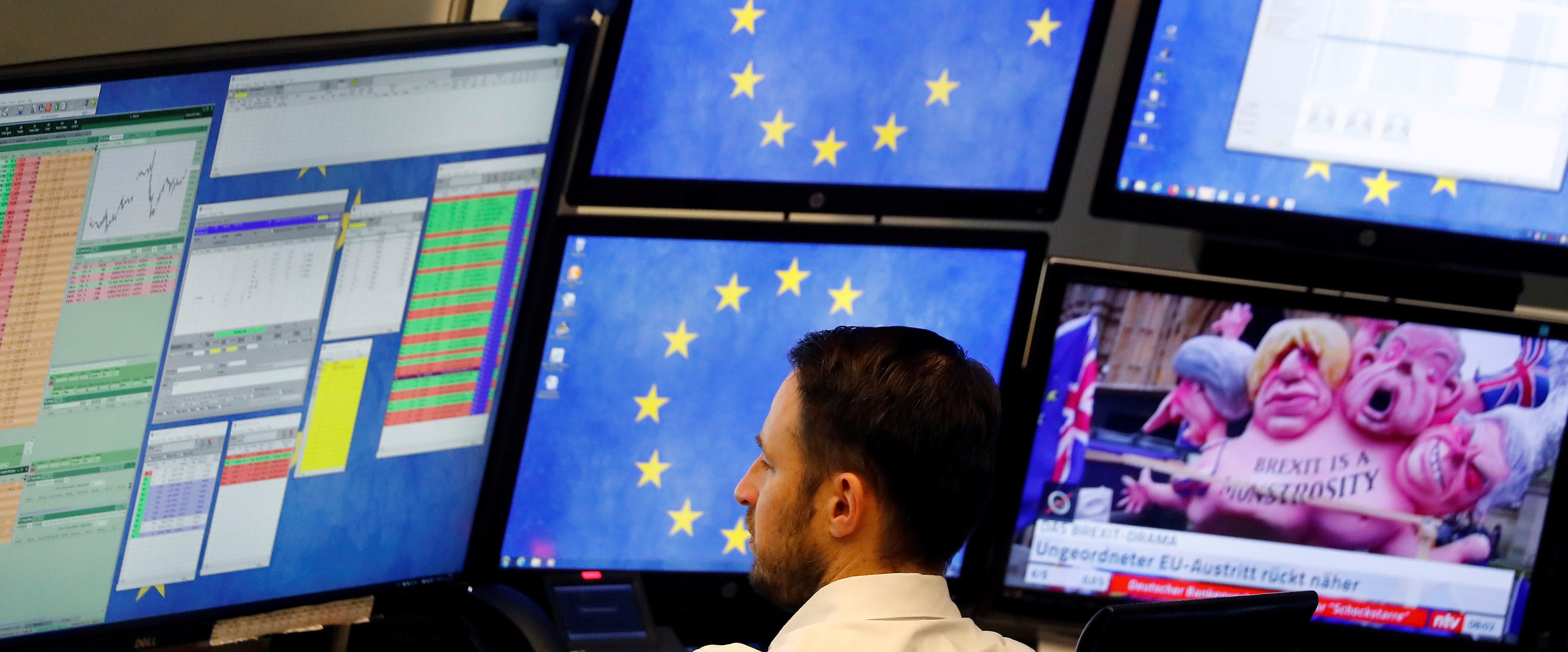 FILE - A shares trader checks his trading systems at the start of the trading session the day after the Brexit deal vote of the British parliament at the stock exchange in Frankfurt, Germany, Jan. 16, 2019.