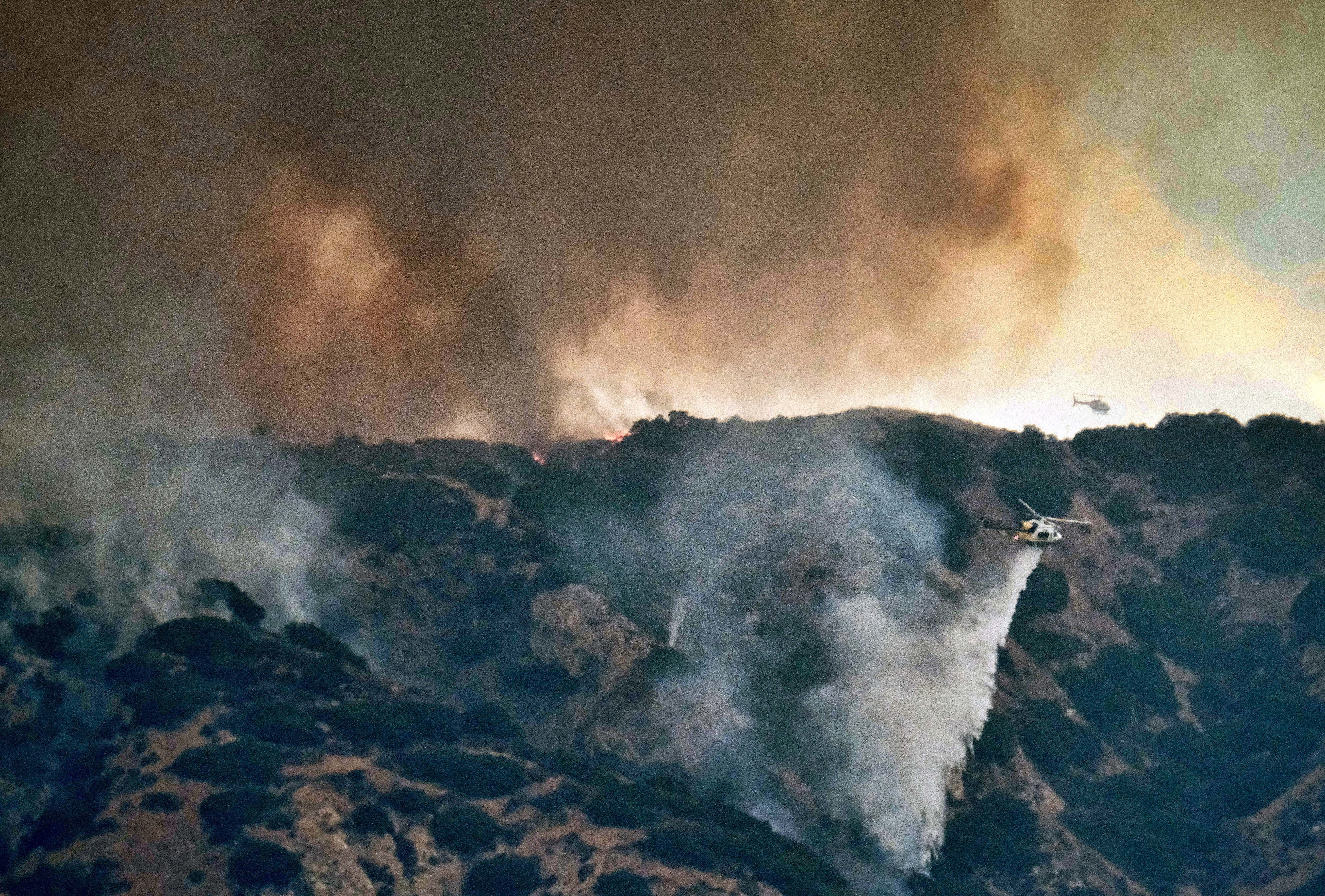 A helicopter makes a water drop amid black smoke rising from a wildfire burning in the Tujunga area of Los Angeles, seen from nearby Burbank, Calif., Sept. 1, 2017. Subdivisions full of houses are within a mile of the flames, and residents of three s...
