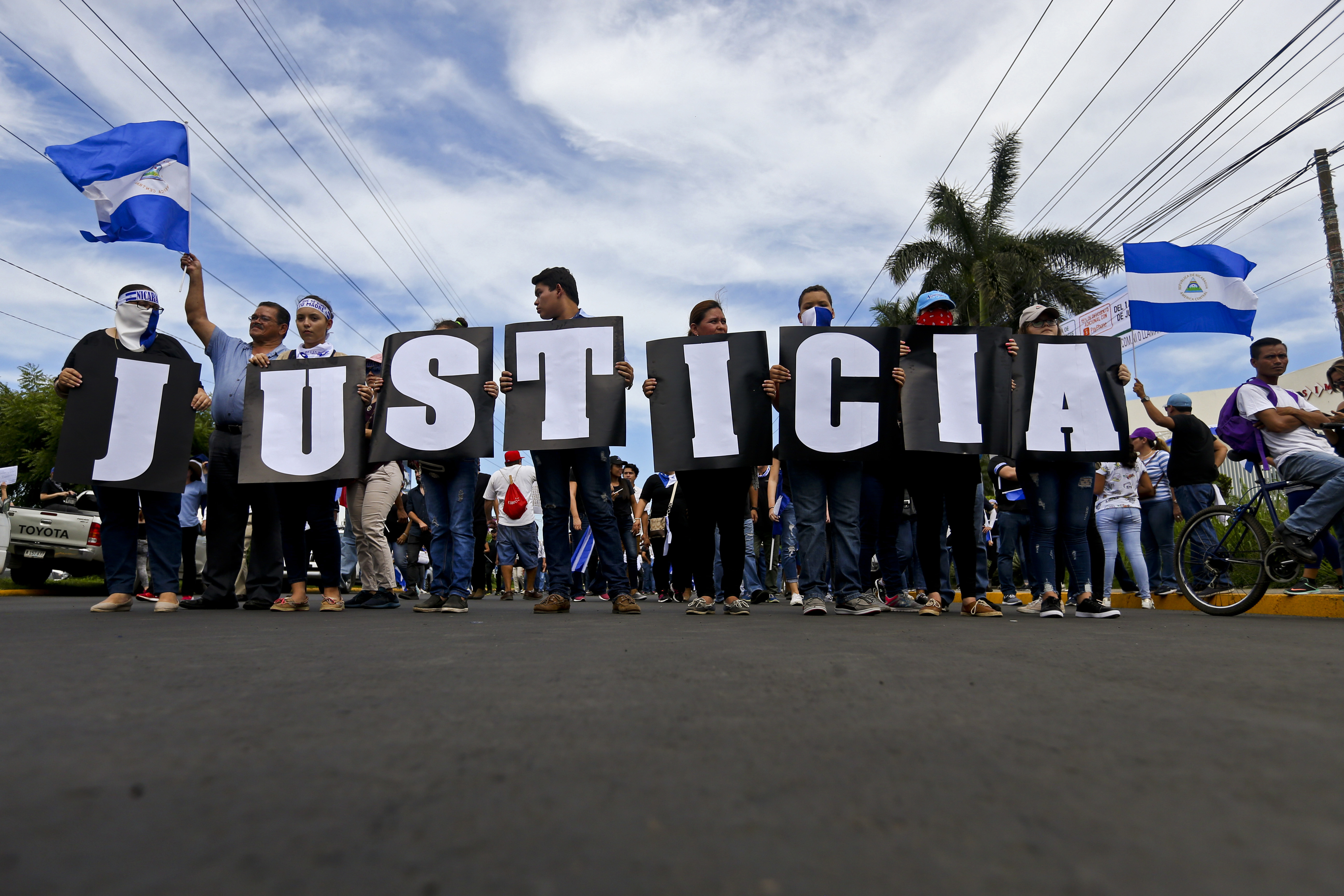 """In this May 30, 2018 photo, anti-government protesters carries letters that form the Spanish word for """"Justice"""" during a march against the government of Nicaragua President Daniel Ortega, and his wife Vice President Rosario Murillo in Managua, Nicara..."""