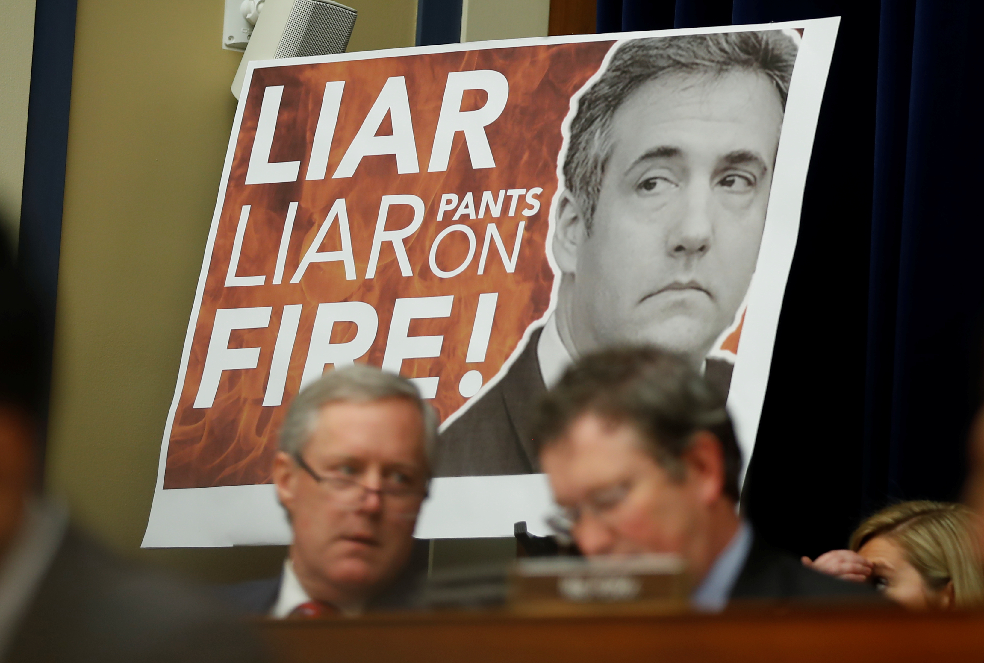 "A sign reading ""Liar Liar Pants on Fire!"" is seen behind Rep. Mark Meadows (R-NC) and other Republican members of the committee during the testimony of former Trump personal attorney Michael Cohen at a House Committee on Oversight and Reform hearing ..."
