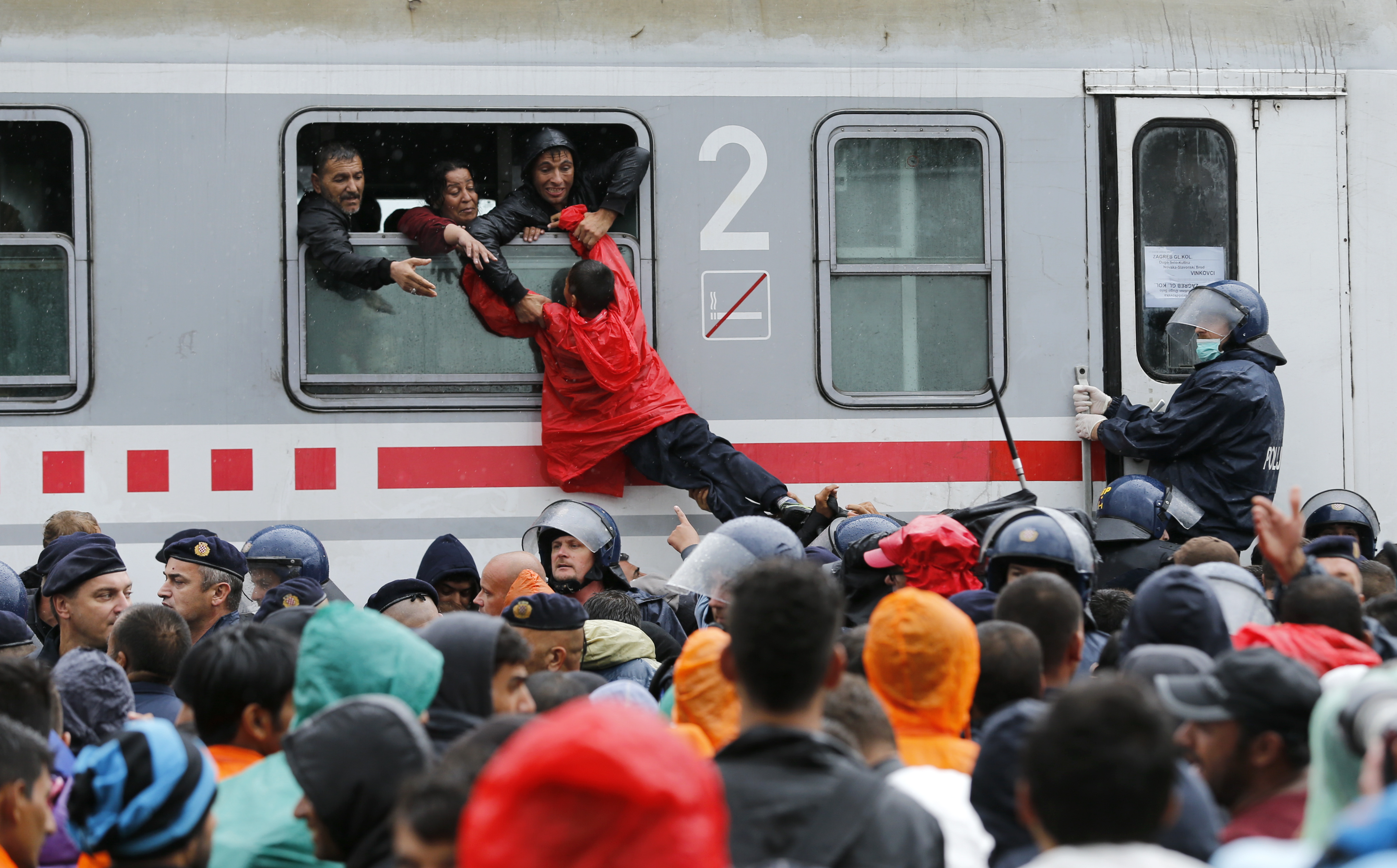 Migrants pull a boy through a train window at the station in Tovarnik, Croatia, Sept. 20, 2015.