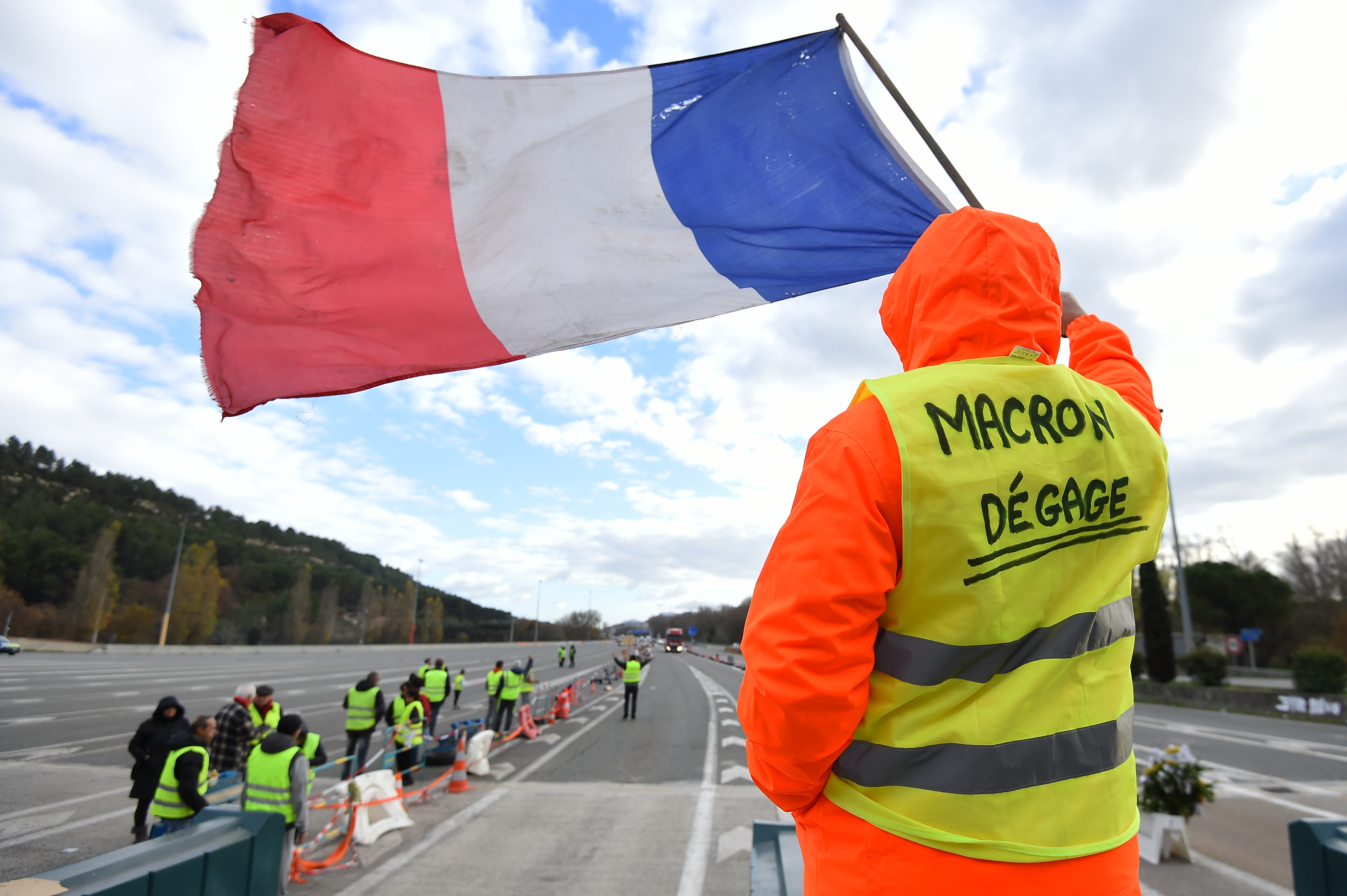 "A man with a sign reading ""Macron resign"" waves a French flag as ""yellow vests"" (Gilets jaunes) protestors gather to protest against rising oil prices and living costs at the highway's toll of La Barque, Dec. 9, 2018, near Marseille, southern France...."