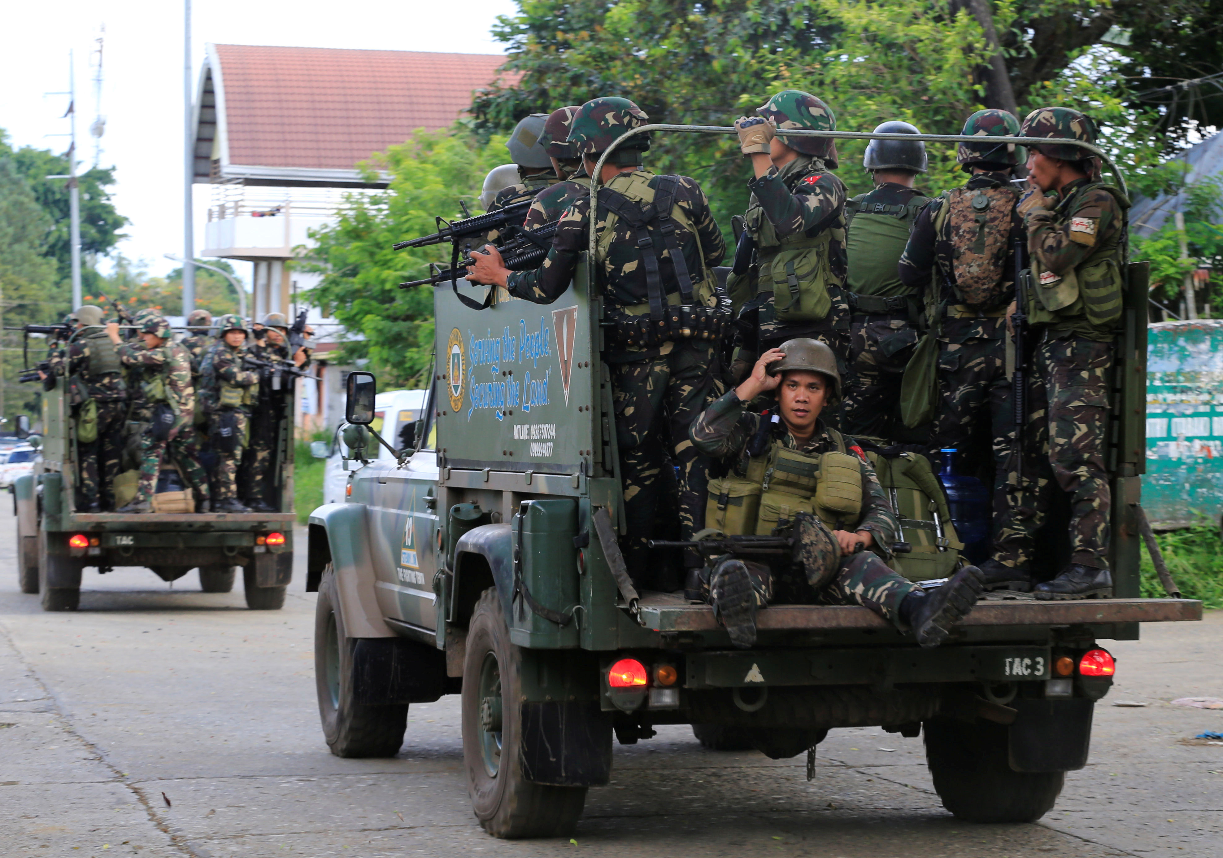 Government soldiers are seen onboard military vehicles driving along the main road of Amai Pakpak as the assault continues against insurgents from the Maute group, who have taken over large parts of Marawi City, Philippines, June 13, 2017.