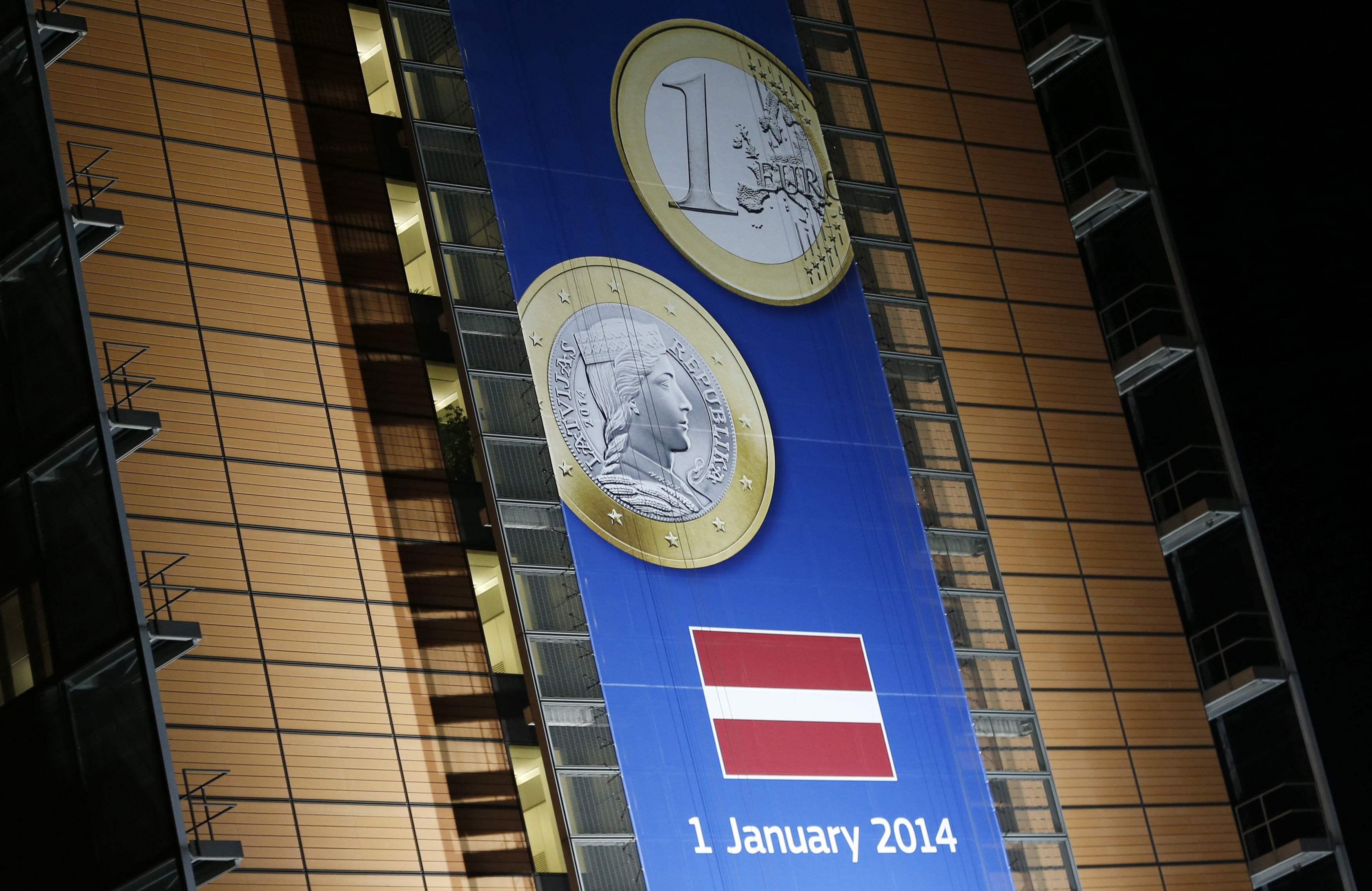 A banner showing a Latvian euro coin is seen on the facade of the European Commission headquarters in Brussels Dec. 20, 2013.