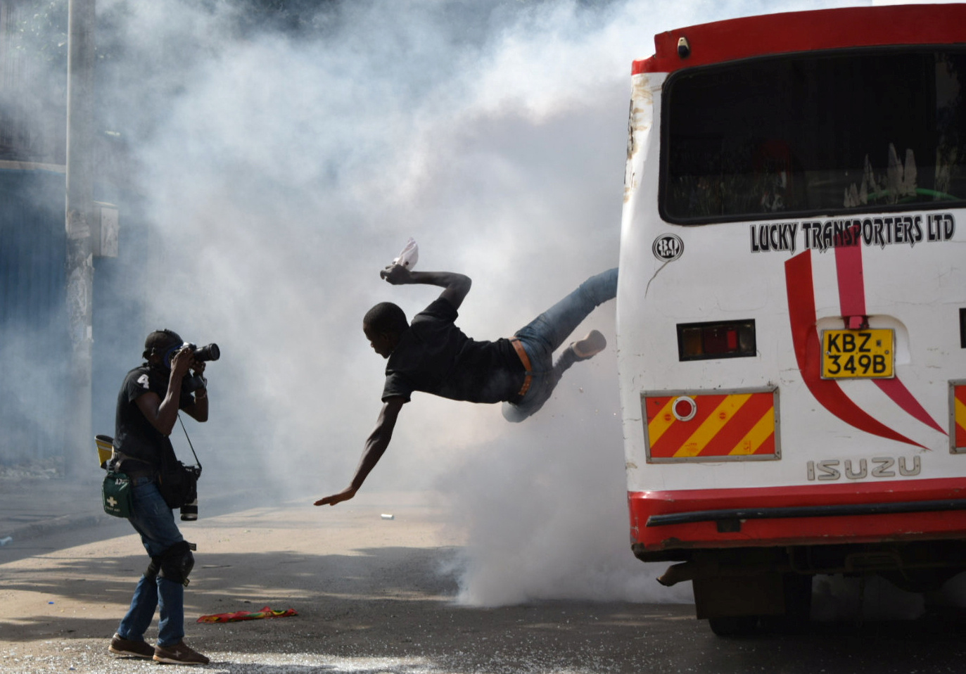 A supporter of Kenyan opposition leader Raila Odinga of the National Super Alliance (NASA) coalition jumps from a bus after riot police fired teargas canisters to disperse them after his swearing-in ceremony in Nairobi, Kenya January 30, 2018.