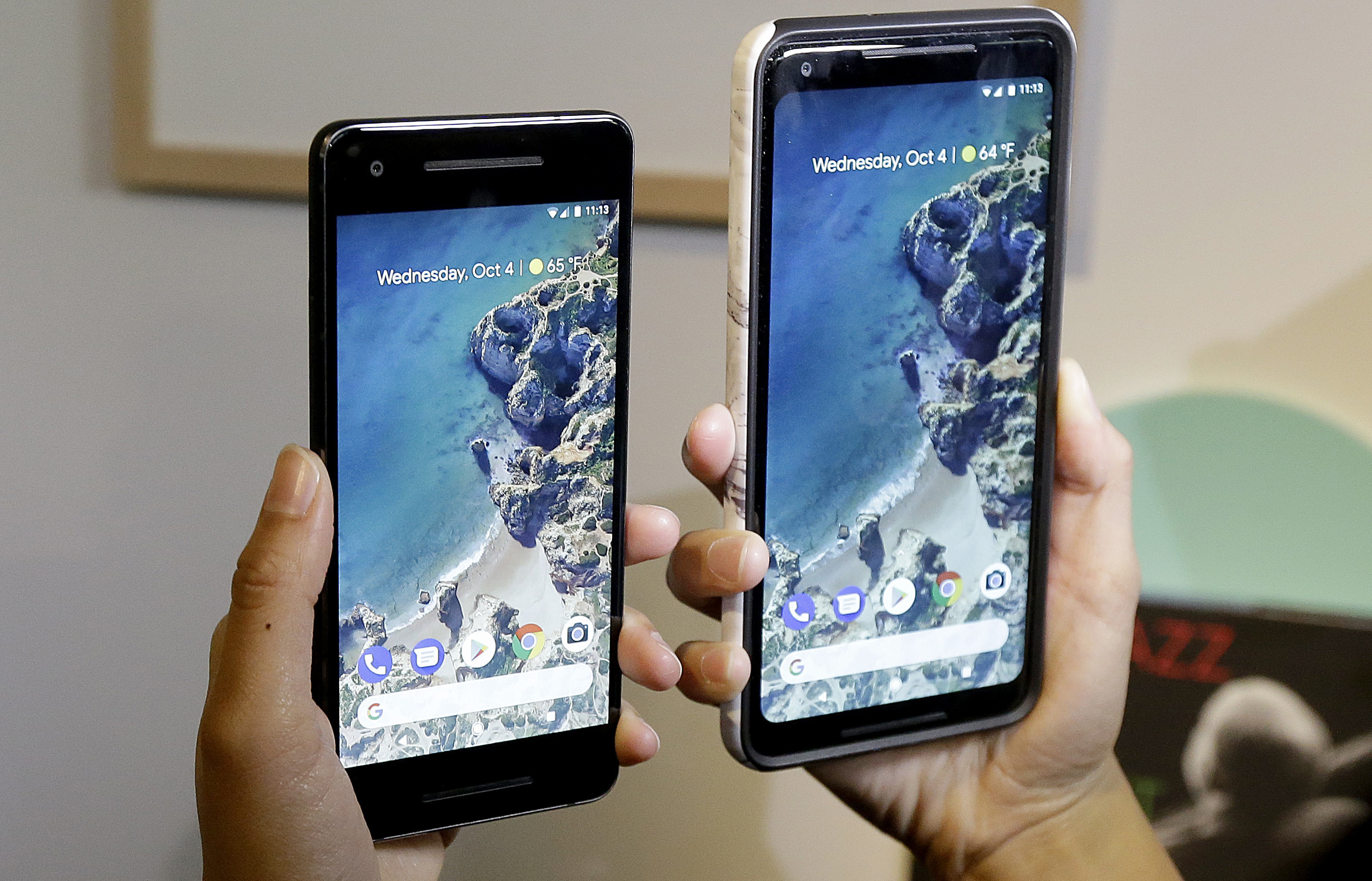 FILE - A woman holds up the Google Pixel 2 phone, left, next to the Pixel 2 XL phone at a Google event at the SFJAZZ Center in San Francisco, Oct. 4, 2017.
