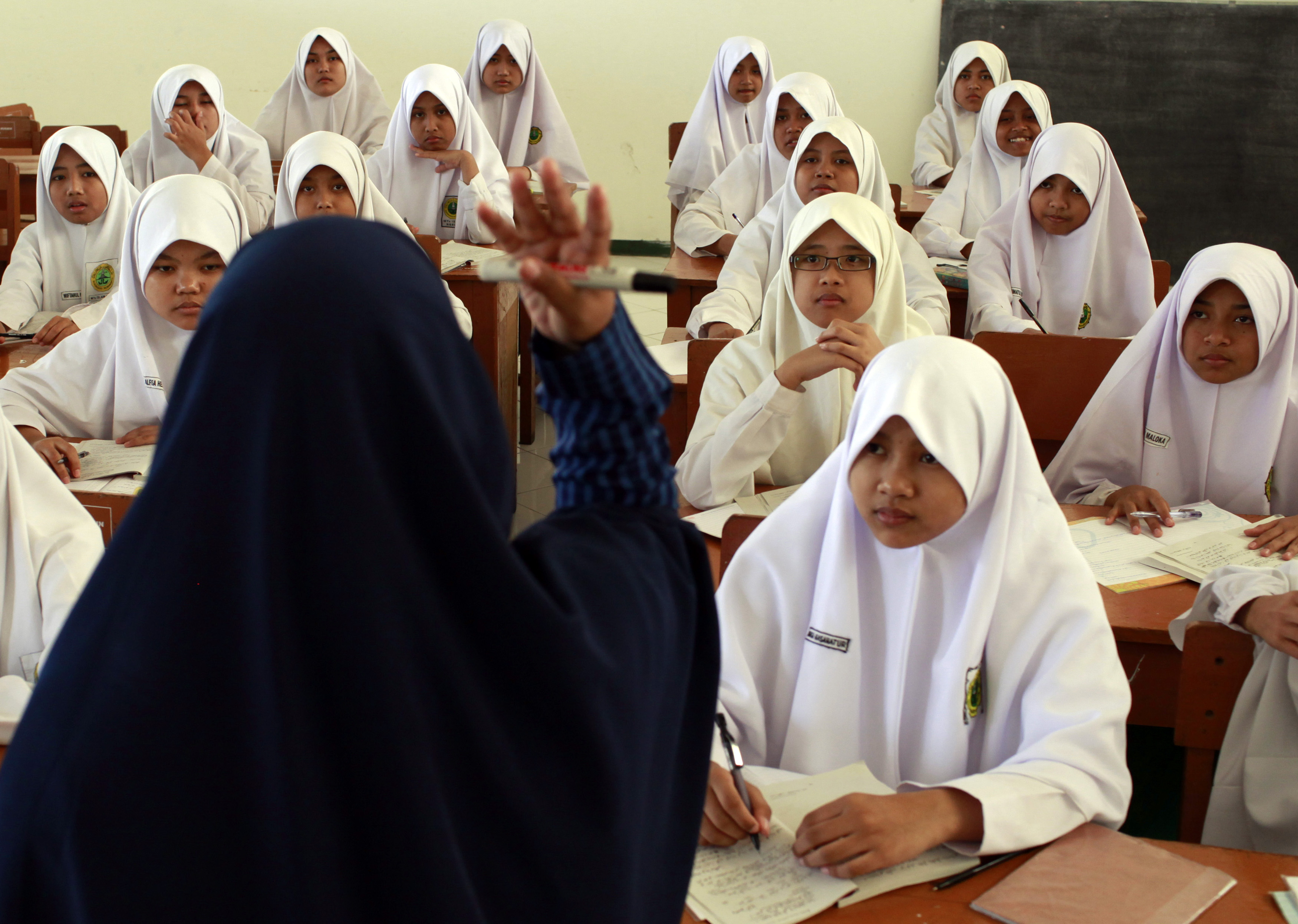 A teacher gestures during an Islam personality class during the holy month of Ramadan at the Al-Mukmin Islamic boarding school in Solo, Indonesia Central Java province, Aug. 2, 2011.