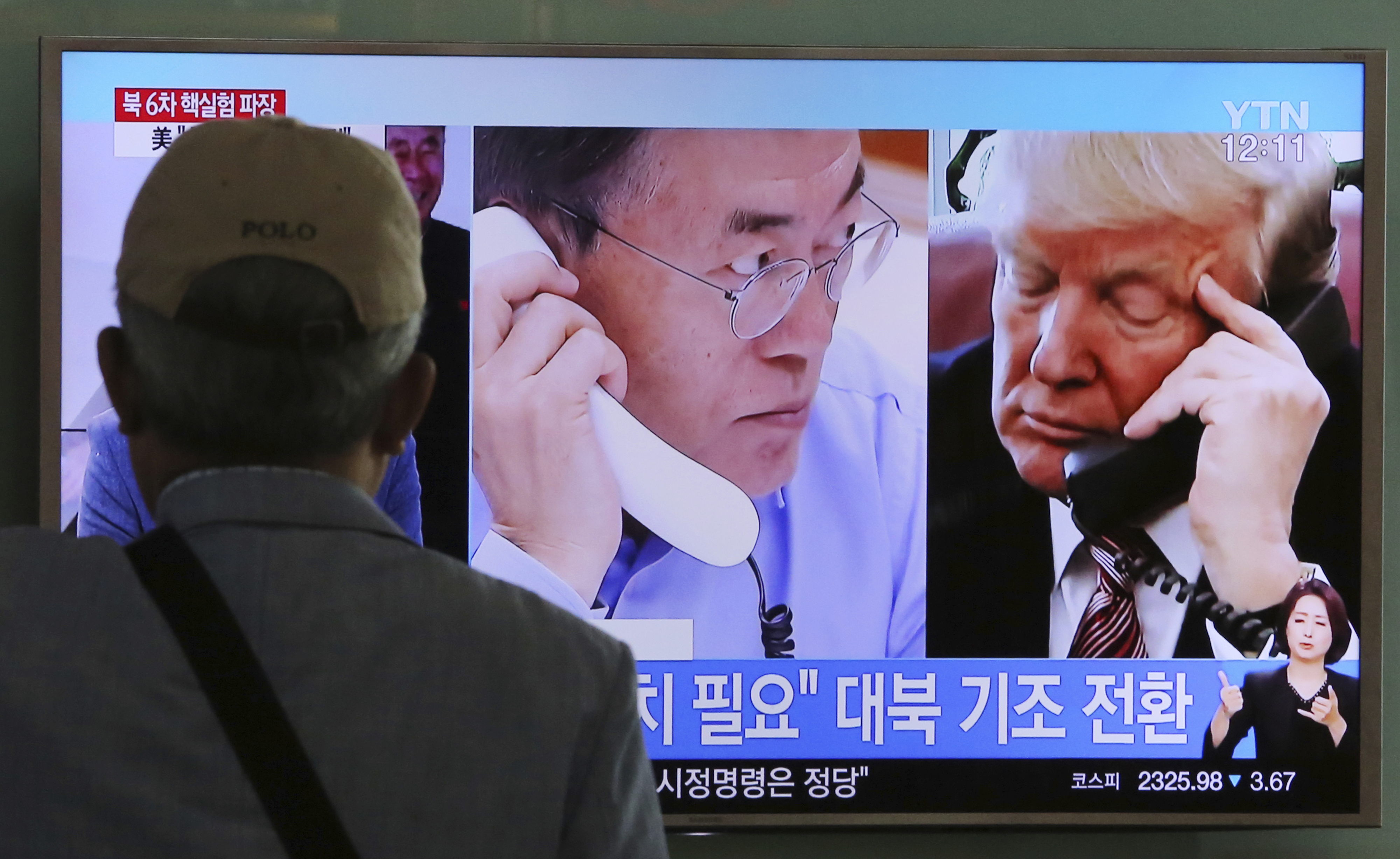 A man watches a TV screen showing U.S. President Donald Trump, right, and South Korean President Moon Jae-in during a news program at the Seoul Railway Station in South Korea, Sept. 5, 2017.