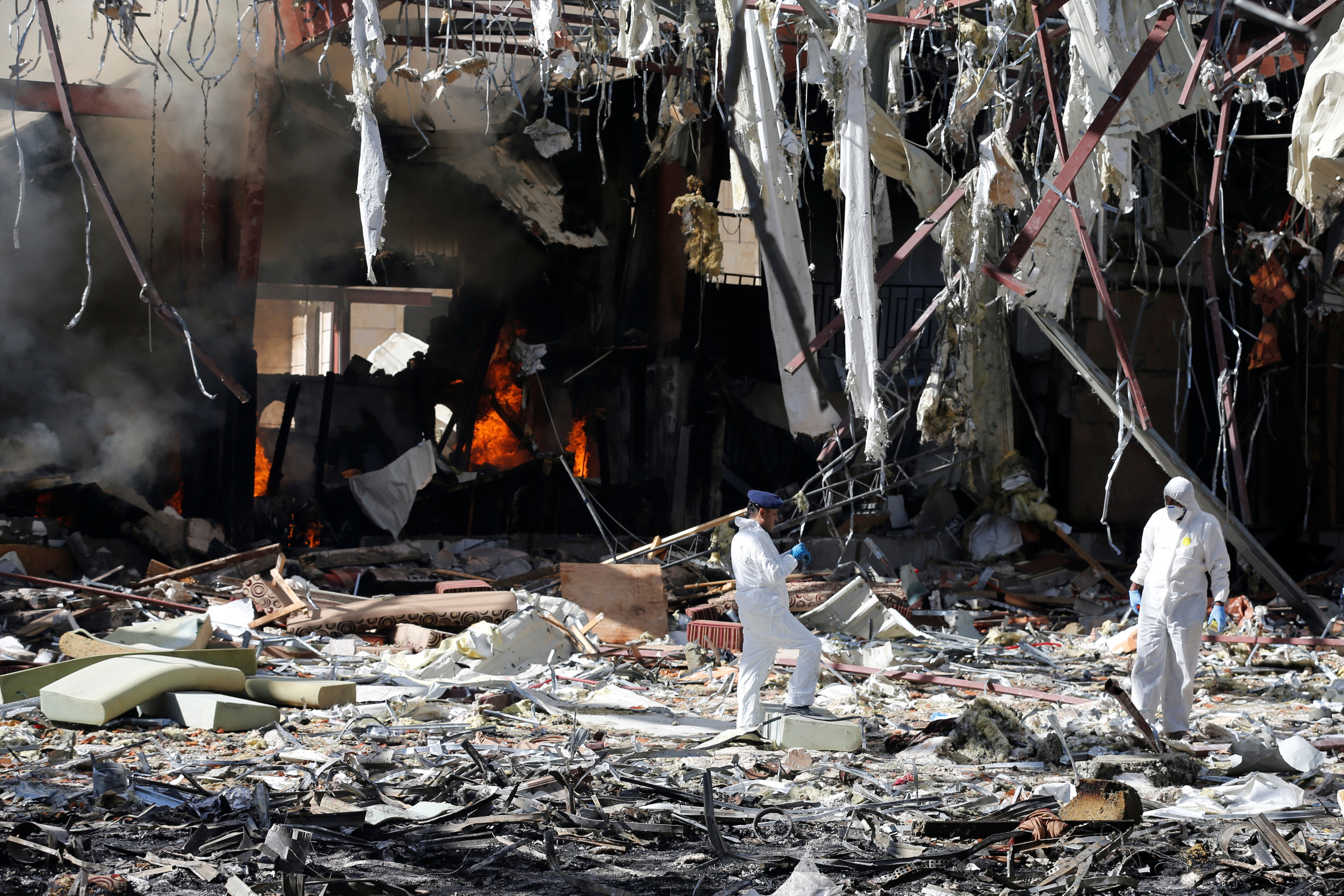 Forensic experts investigate the scene at the community hall where Saudi-led warplanes struck a funeral in Sanaa, the capital of Yemen, October 9, 2016.