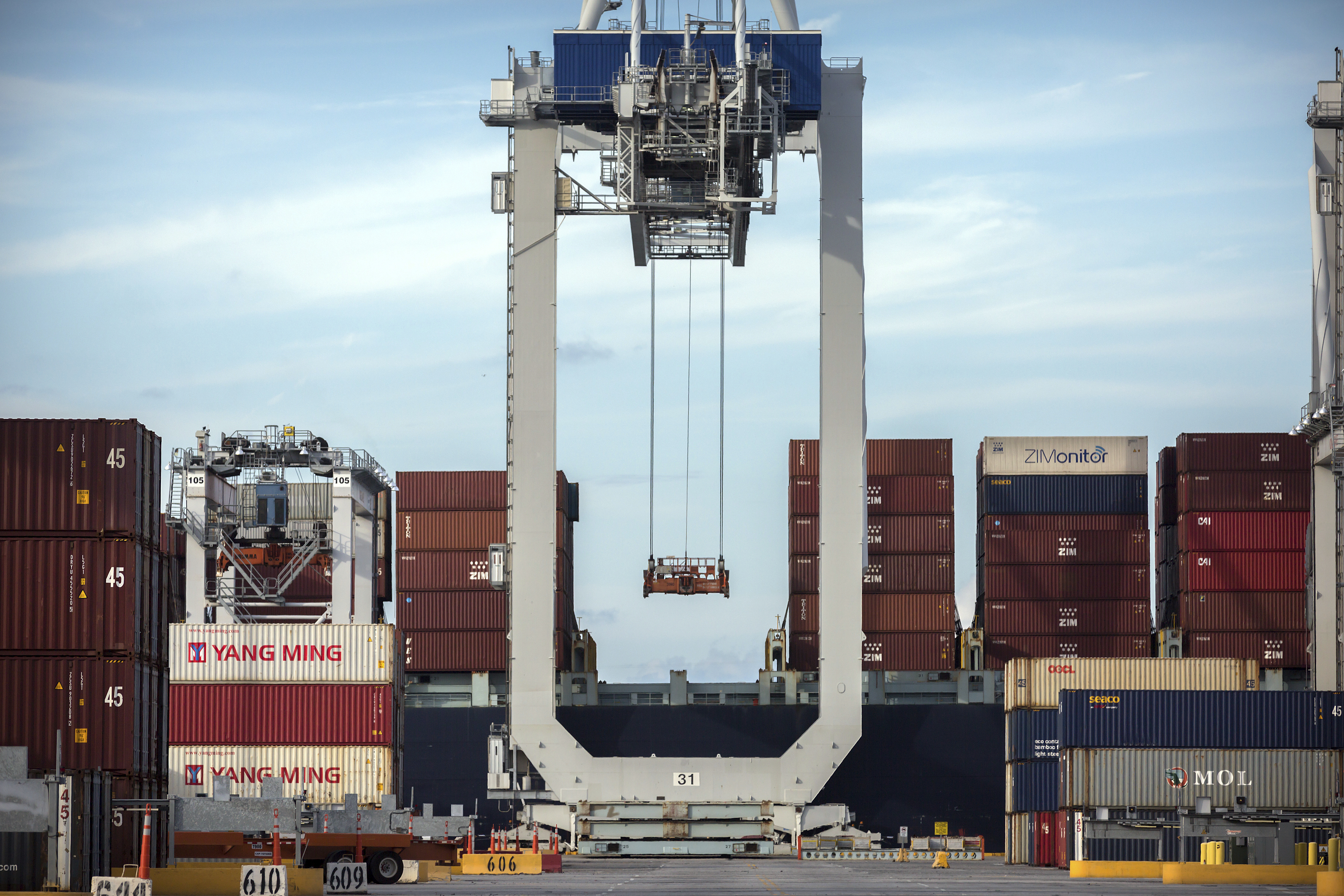 FILE - A ship-to-shore crane prepares to load a 40-foot shipping container onto a container ship at the Port of Savannah in Savannah, Georgia, July 5, 2018.