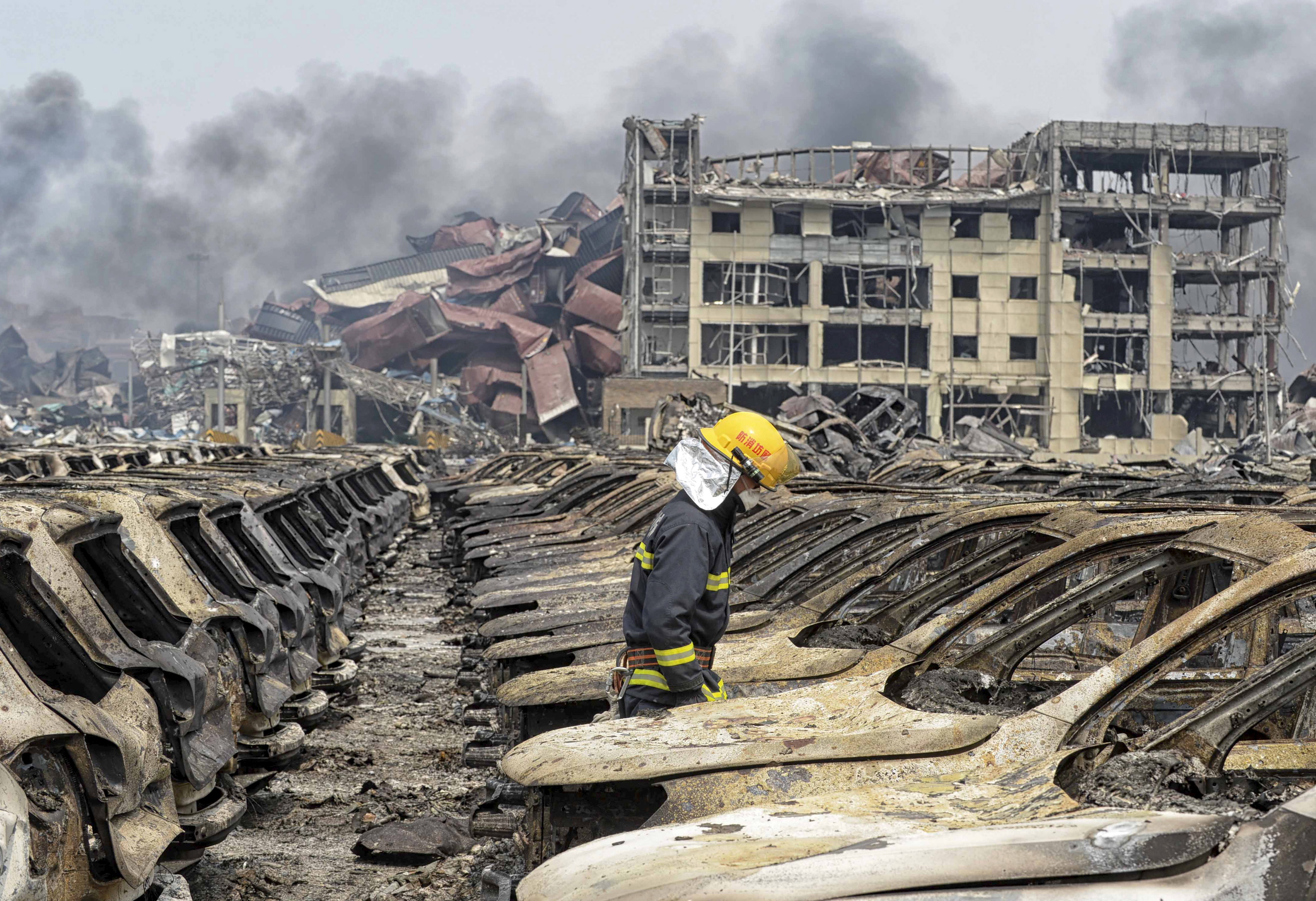 A firefighter walks among damaged vehicles as smoke rises amidst shipping containers at the site of explosions, at Binhai new district in Tianjin, China, Aug. 14, 2015.