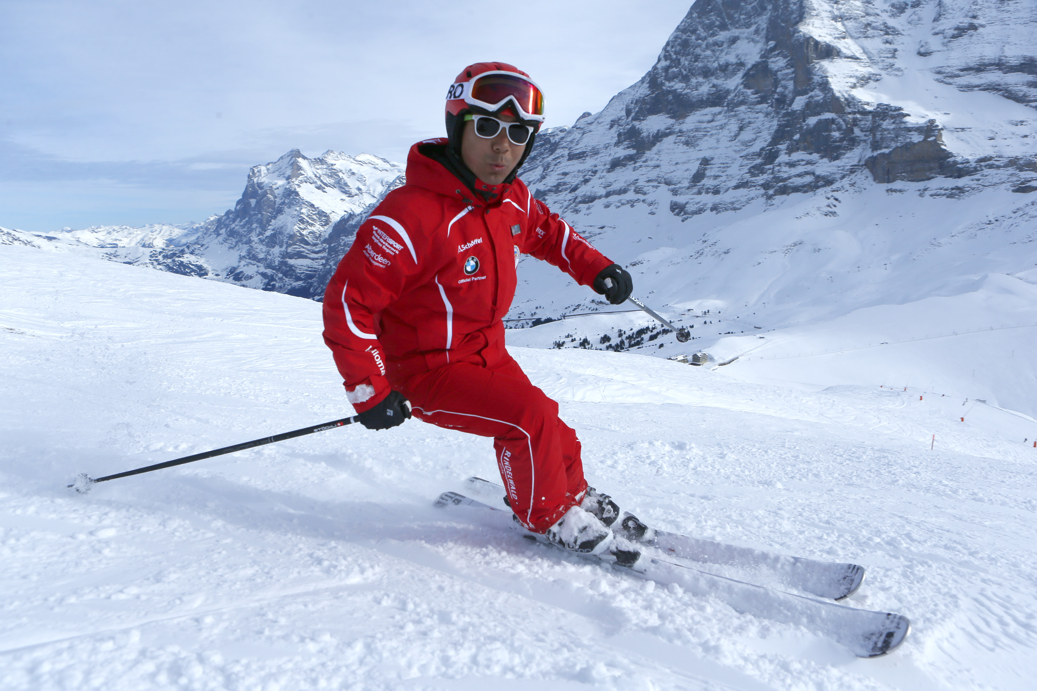 Chinese ski instructor Xu Zhongxing (L) skis on the Lauberhorn in front of the Eiger north face in the ski resort of the Jungfrau region, Jan. 8, 2014.