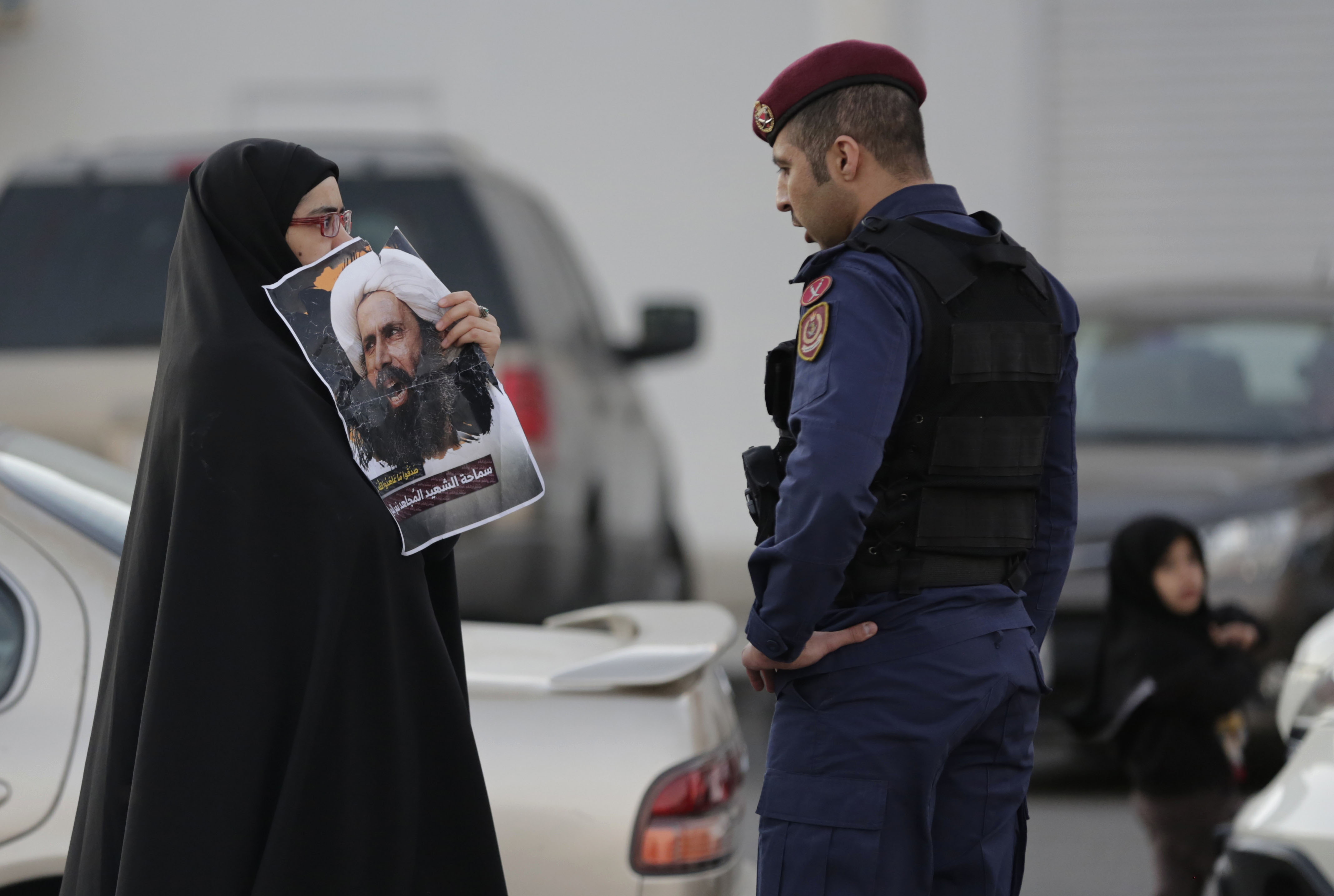 A Bahraini protester holds up a picture of Saudi Shi'ite cleric Sheikh Nimr al-Nimr in front of a riot police officer in Daih, Bahrain, a largely Shi'ite suburb of the capital, Jan. 4, 2016.