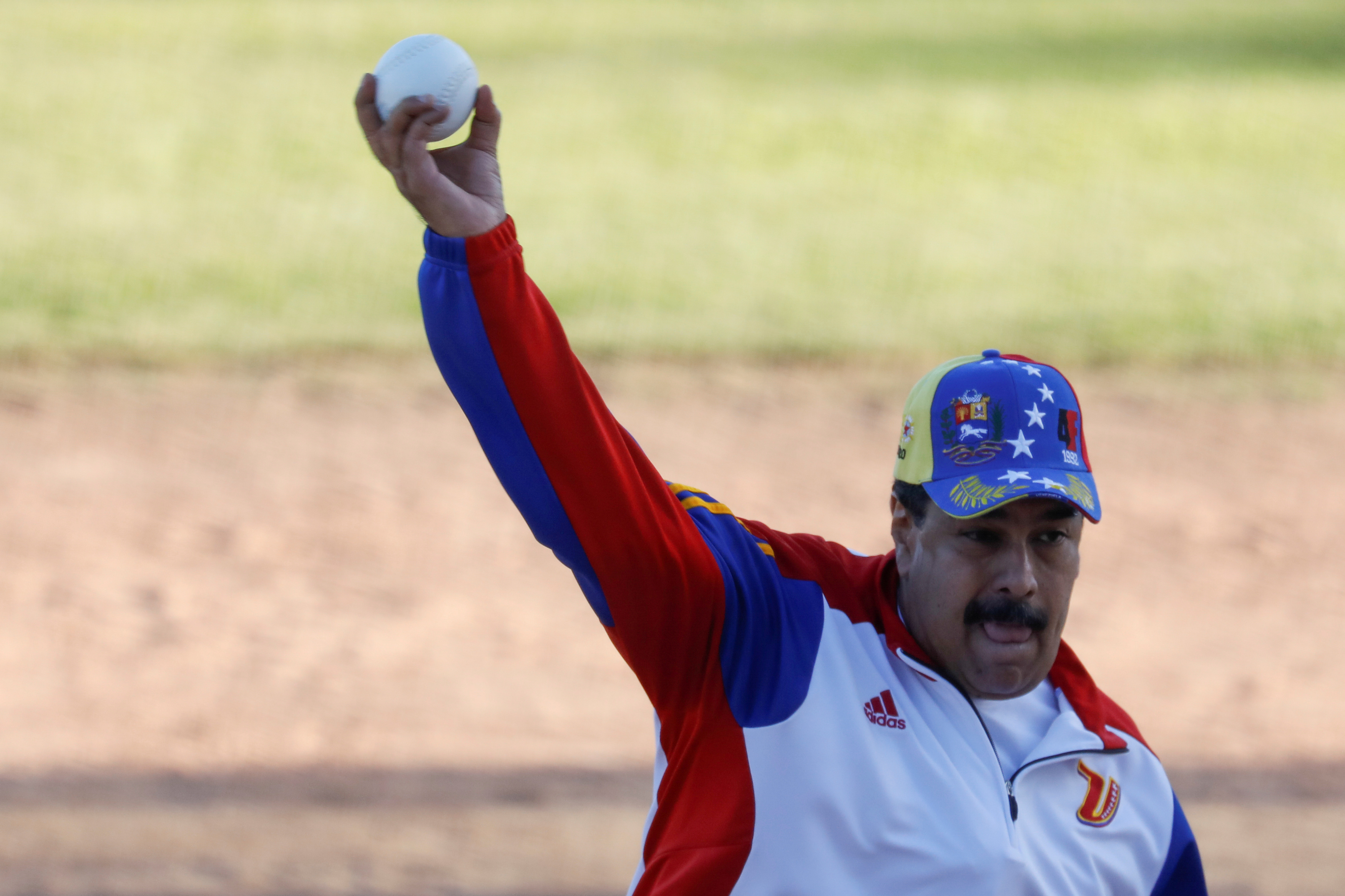 Venezuela's President Nicolas Maduro throws the ball during a softball game with ministers and military high command members at Fuerte Tiuna military base, in Caracas, Venezuela, Jan. 28, 2018.
