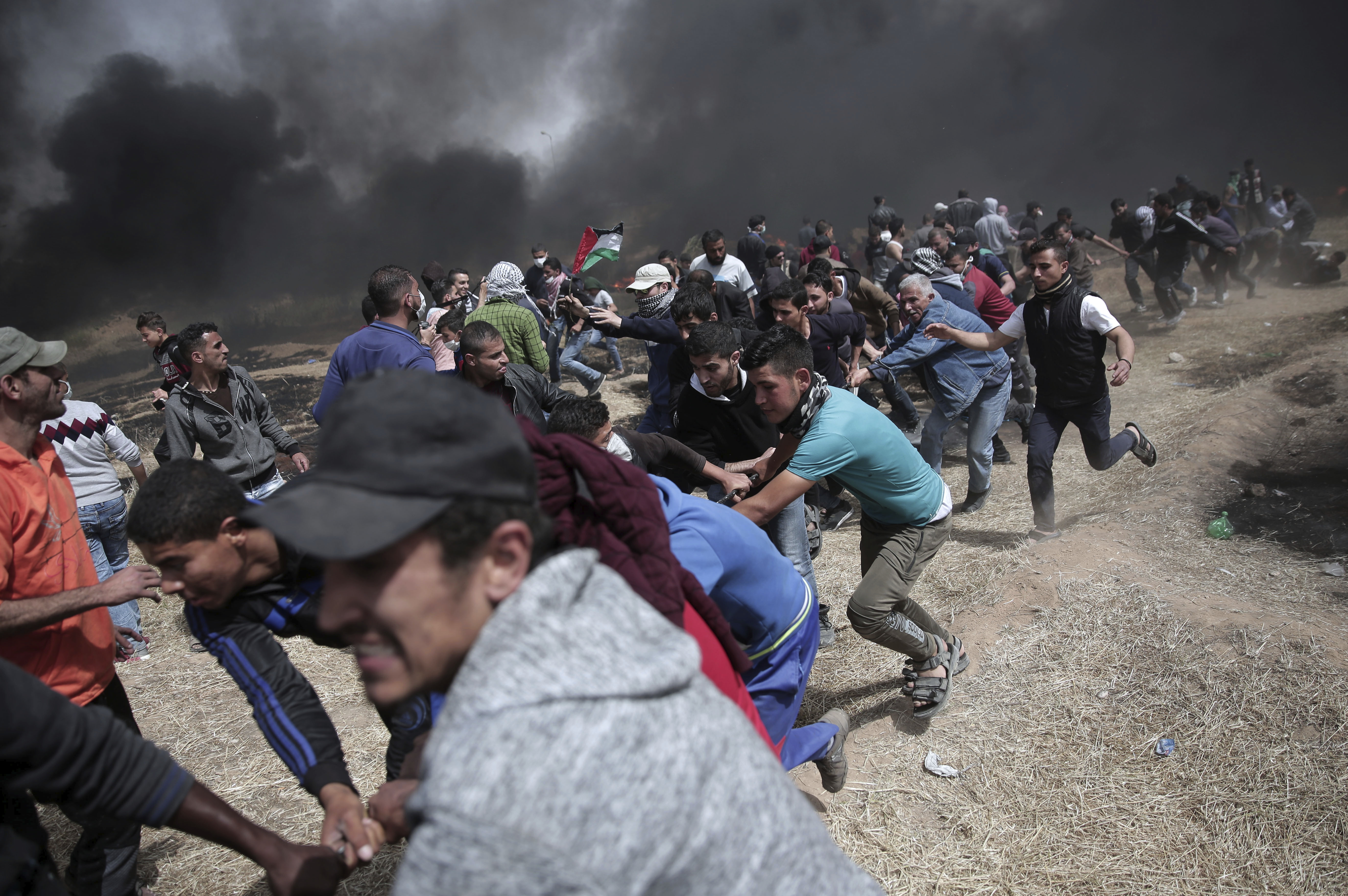 Palestinian protesters chant slogans as they pull part of the fence that the Israeli Army placed, during a protest at the Gaza Strip's border with Israel, April 13, 2018.
